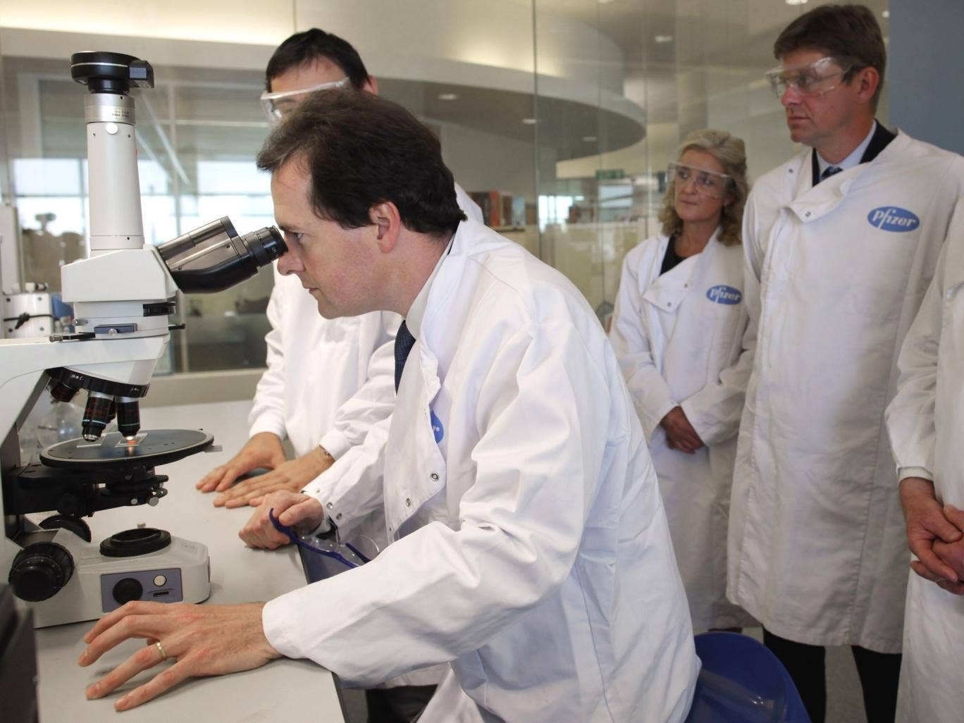 Chancellor George Osborne looks through a microscope at Pfizer's pharmaceutical science lab in 2011