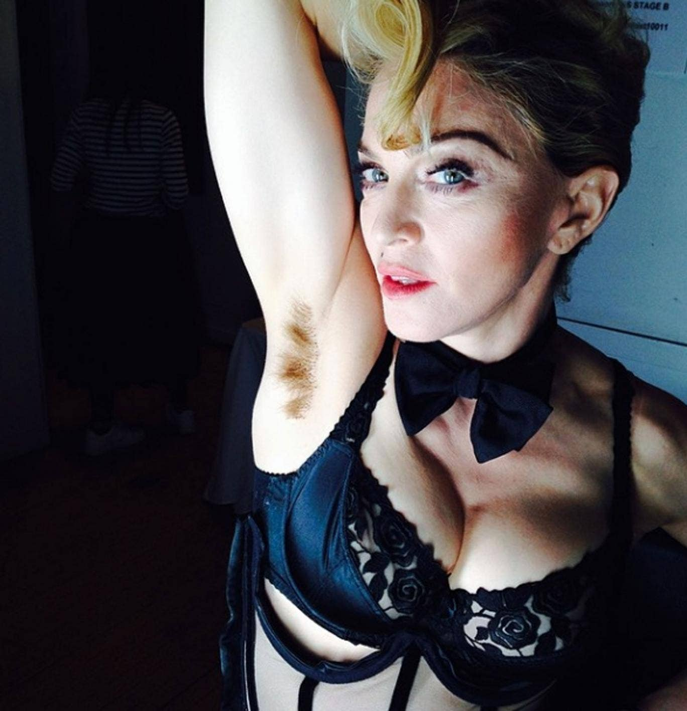 Madonna holds up her right arm to reveal her unshaven armpit