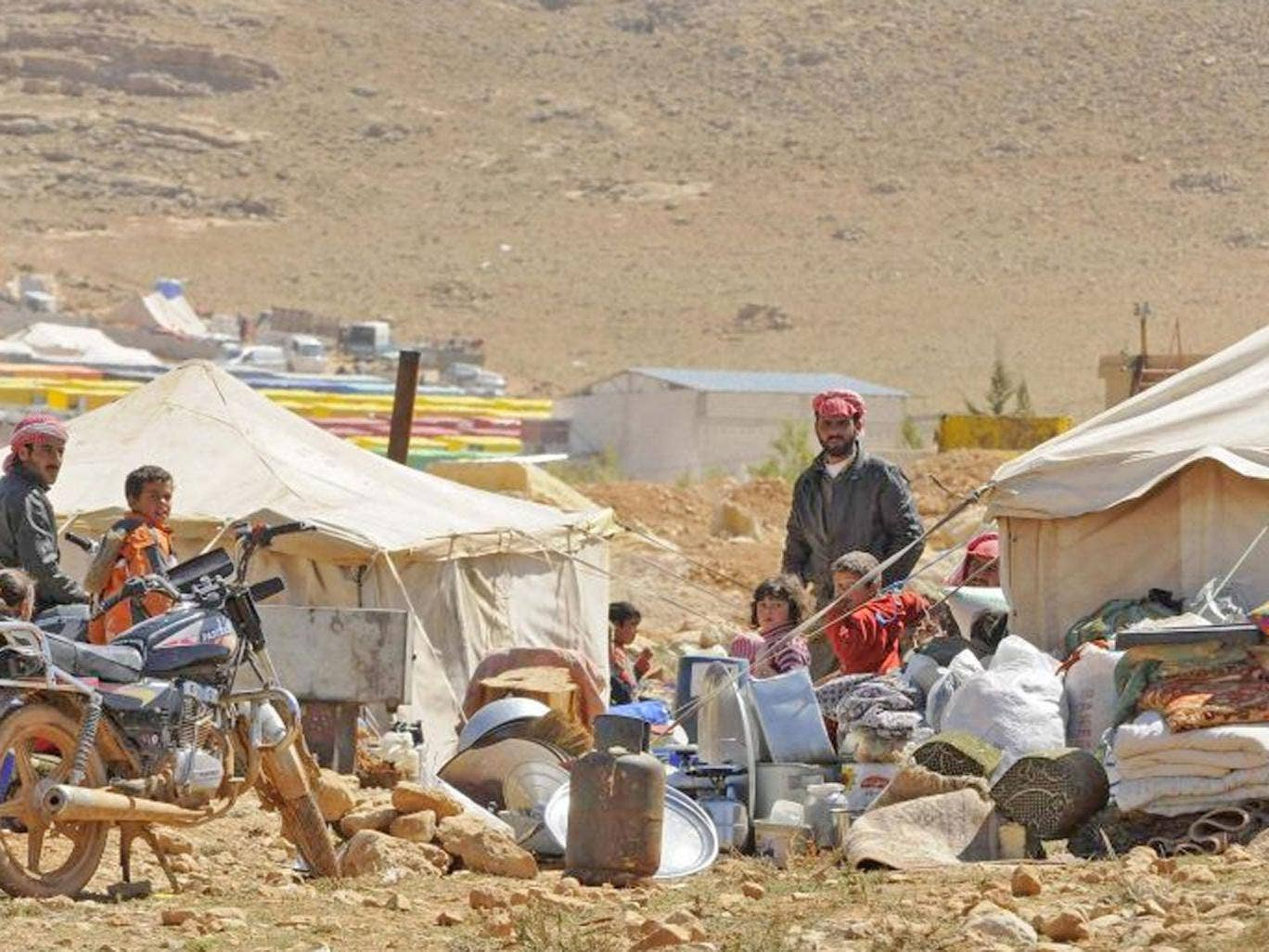 Refugees who fled the violence from the Syrian town of Flita, near Yabroud, stand outside their tents at the border town of Arsal, in the eastern Bekaa Valley. The first of 'several hundred' Syrian refugees to be brought to Britain as part of a Government