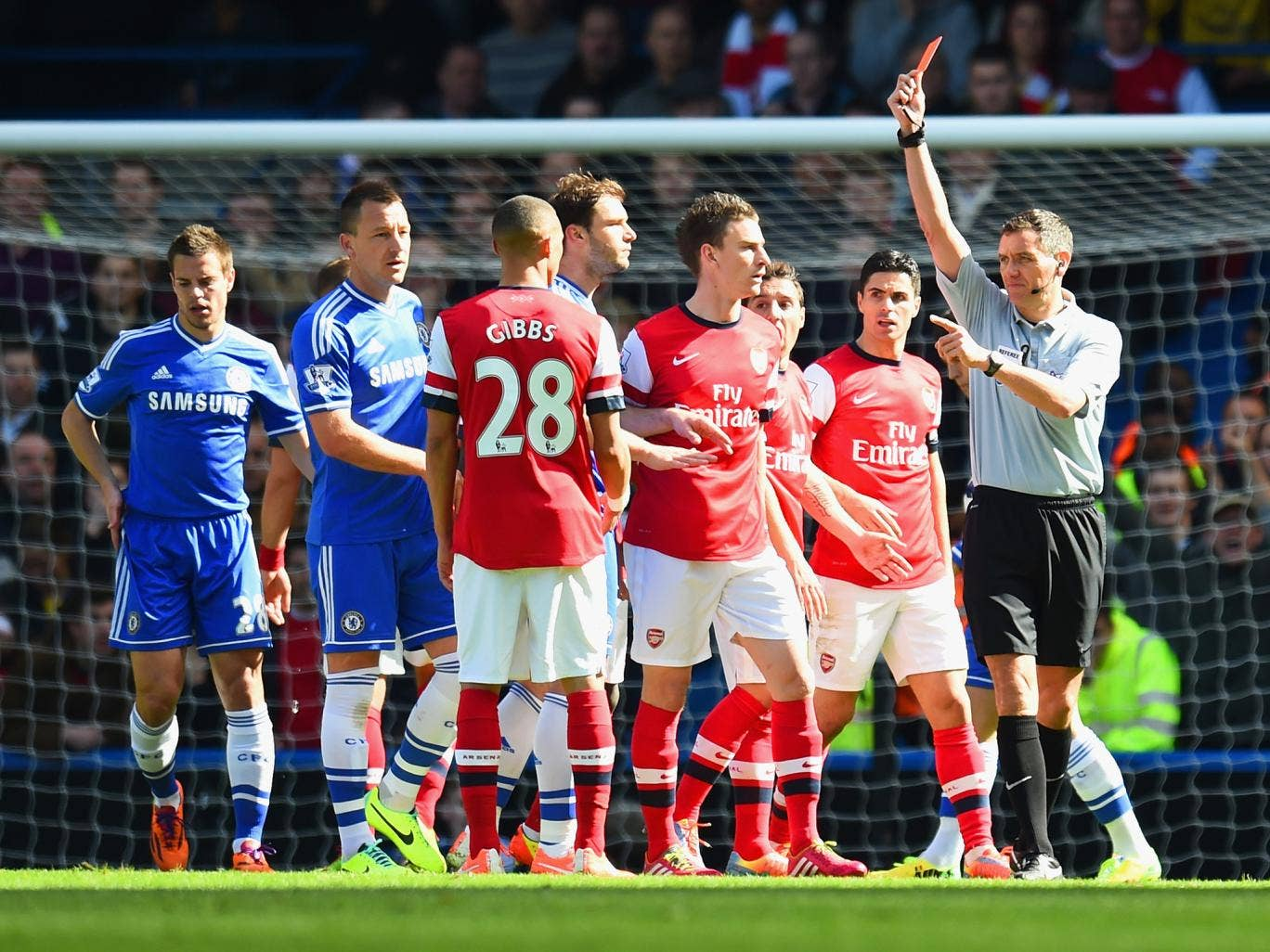 Kieran Gibbs is wrongly shown a red card by referee Andre Marriner