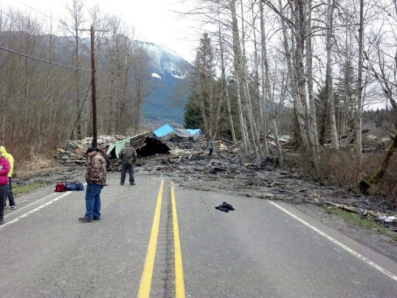 An image released by the Washington State Patrol shows emergency workers assisting at the scene of a mudslide which destroyed several homes and killed at least three people