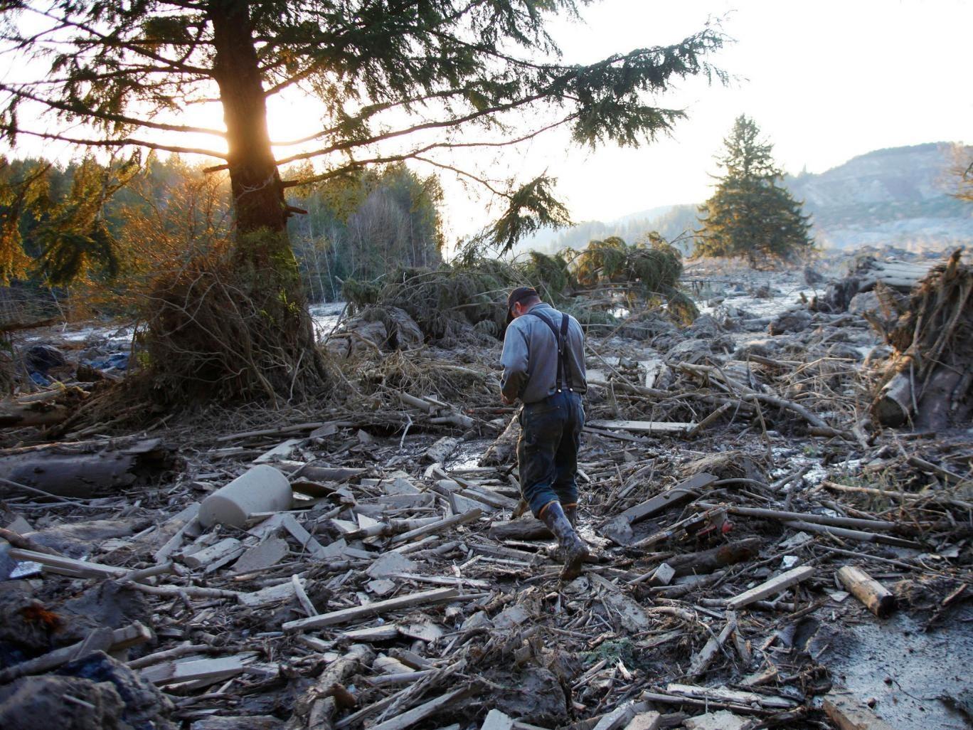 Steve Skaglund walks across the rubble on the east side of Saturday's fatal mudslide near Oso, Wash., Sunday, March 23