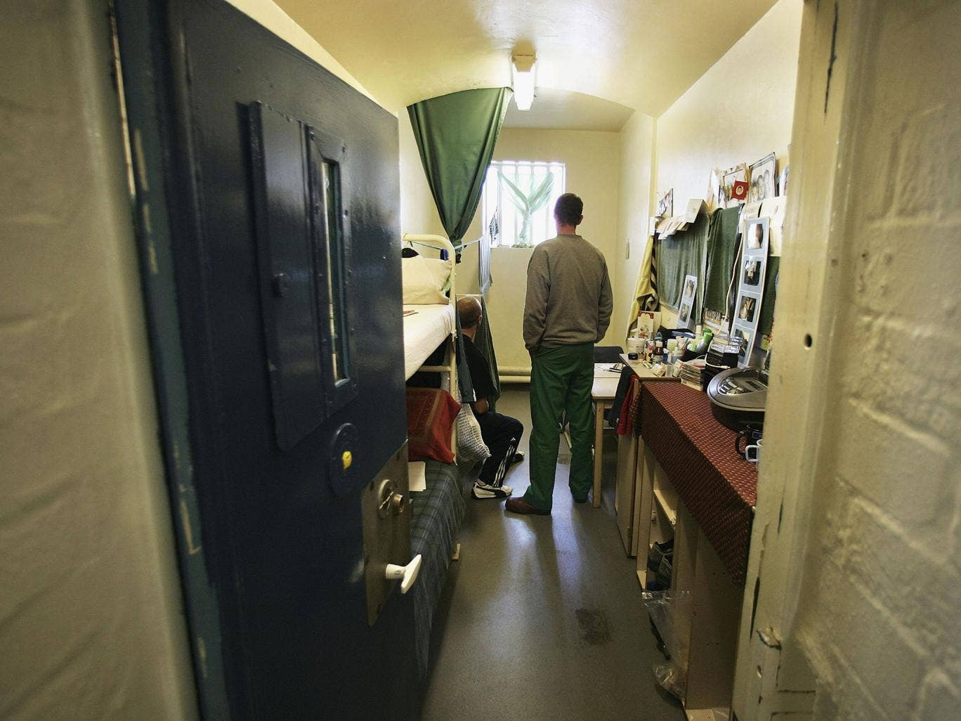 Prisoners look towards a window in a cell in A Wing of Norwich Prison on August 25, 2005 in Norwich, England. A Chief Inspector of Prisons report on Norwich Prison says healthcare accommodation was among the worst seen, as prisoners suffered from unscreen