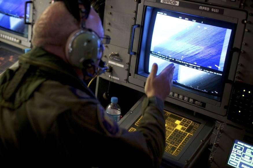 A crew member on board an RAAF AP-3C Orion aircraft looks at a radar screen whilst searching for missing Malaysia Airlines Flight MH370 over the Indian Ocean