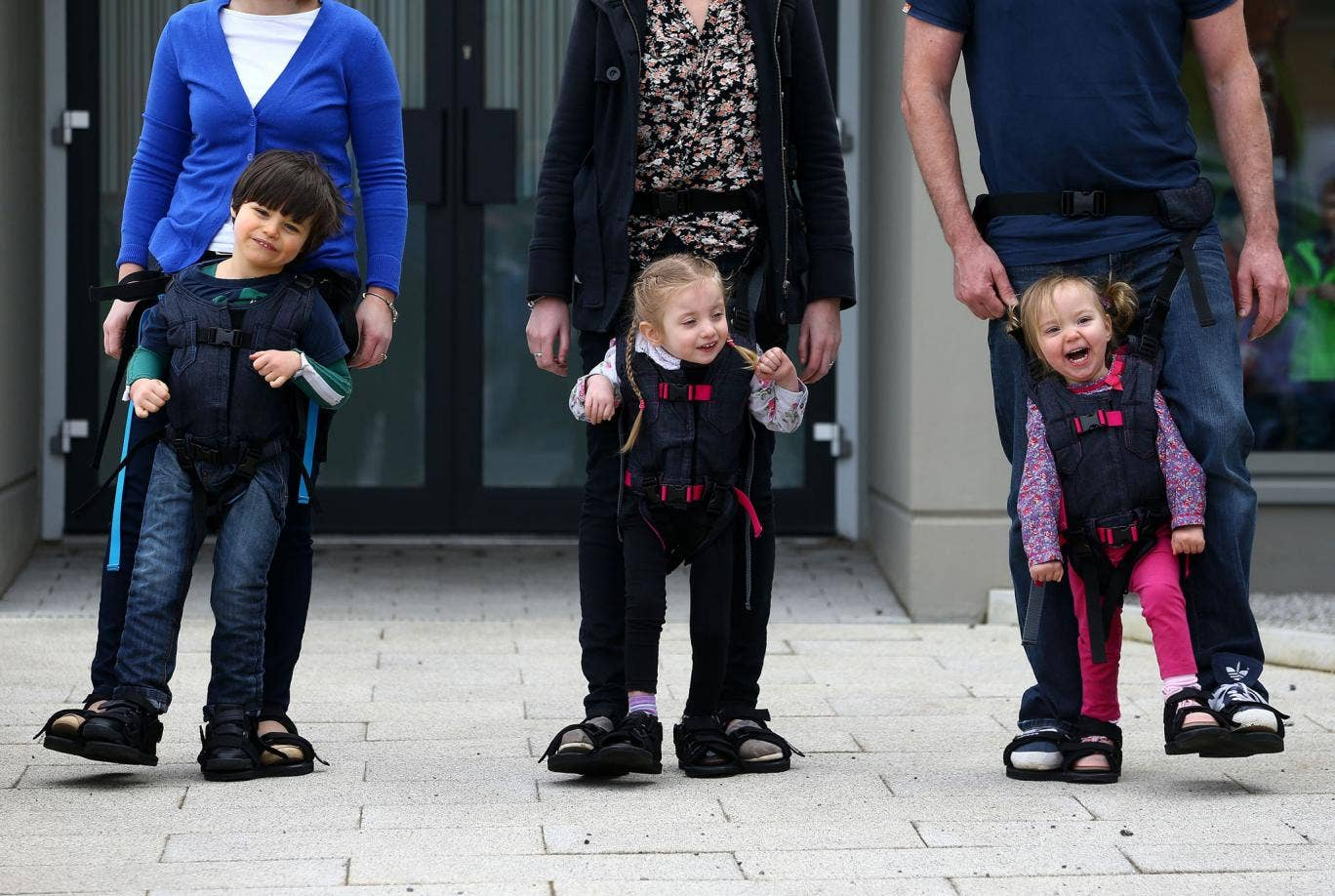 Daniel Smyth, 5, Bethany Watson, 3, and Charlotte Taylor, 3, using a Firefly Upsee, a new standing and walking harness for children with motor impairment, which attaches to a parent, allowing them and their child to take steps together