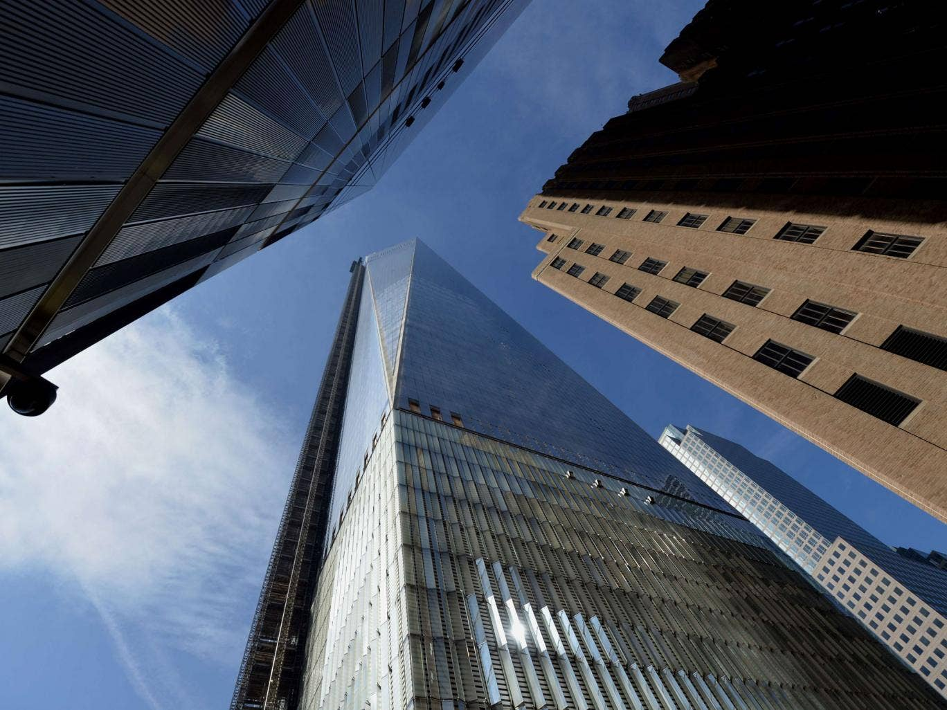One World Trade Center is seen between nearby buildings in Lower Manhattan
