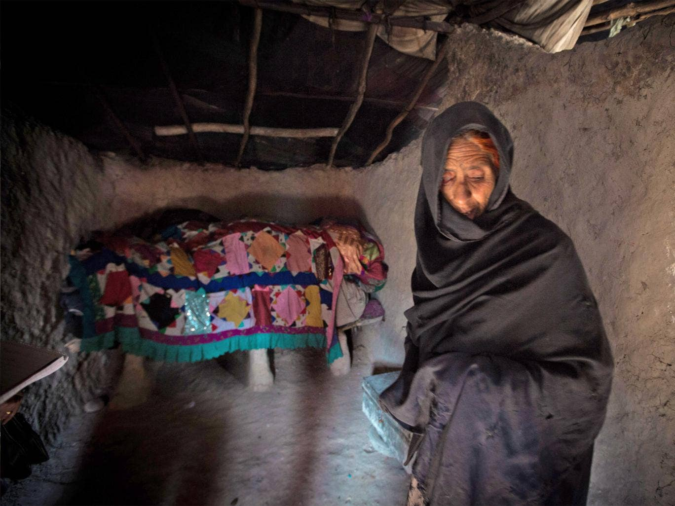 Niaz Bibi shelters in her mud-walled home in Kabul's Nasaji Bagramy camp for internal refugees. Her family survives on charity handouts and the proceeds of her grandchildren's begging