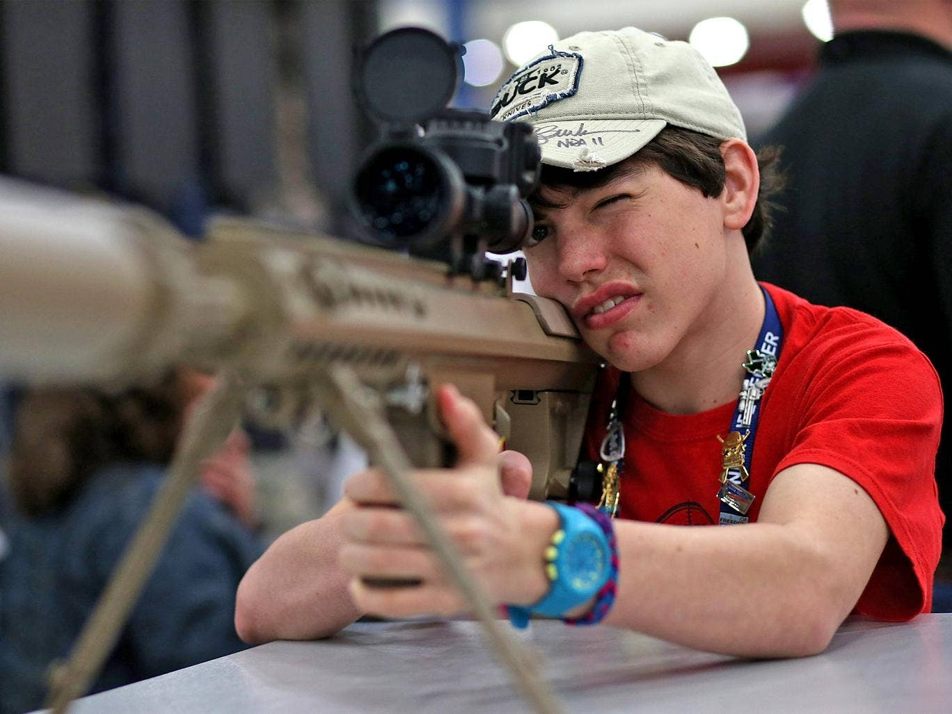 A young boy inspects a high-power sniper rifle at the 2013 NRA annual show