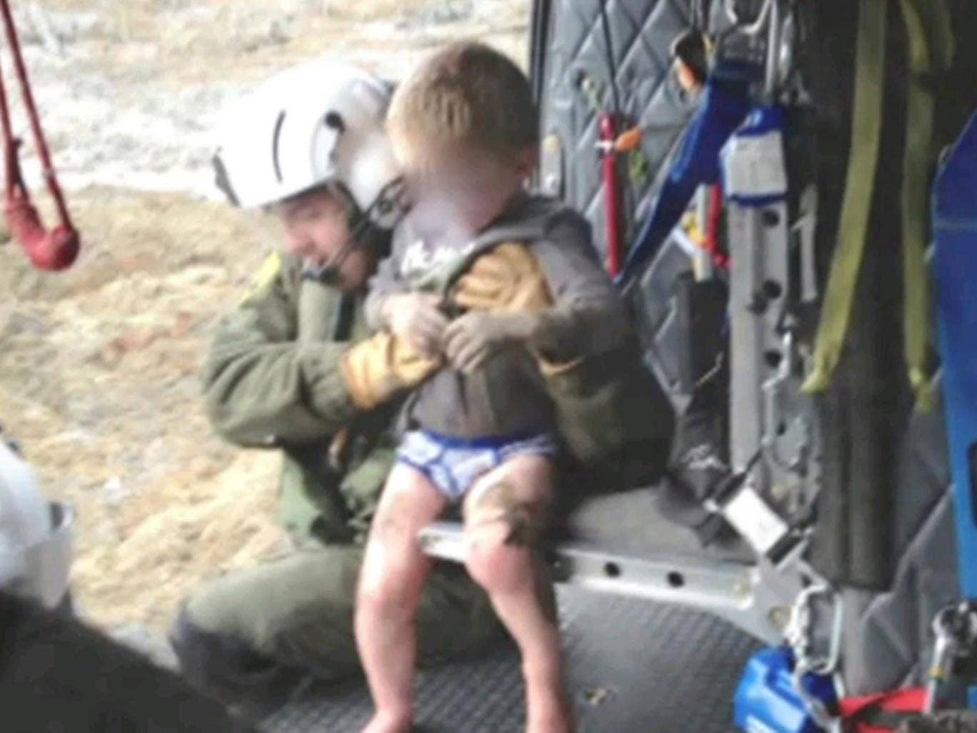 A helicopter rescuer snatches a four-year-old boy from the mudslide