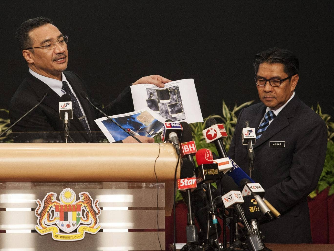 Malaysian Defense Minister and acting Transport Minister Hishammuddin Hussein (L) and Malaysia's Department Civil Aviation Director General, Azharuddin Abdul Rahman (R) show pictures of possible debris during a media conference in Kuala Lumpur