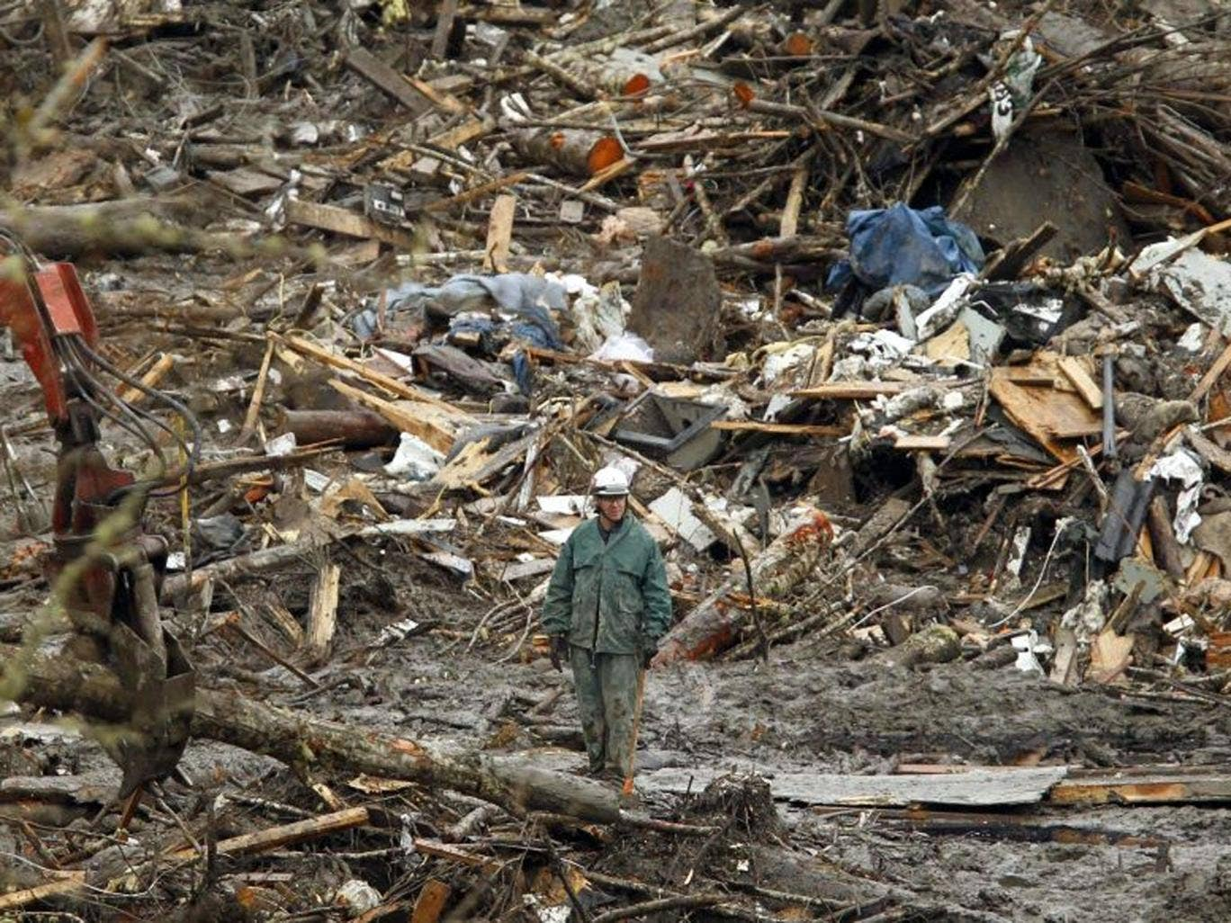 A rescue worker looks over the debris pile from the mudslide in Oso, Washington March 27, 2014. The death toll from a massive Washington state mudslide is expected to climb sharply over the next two days with 90 people still missing, authorities said on T