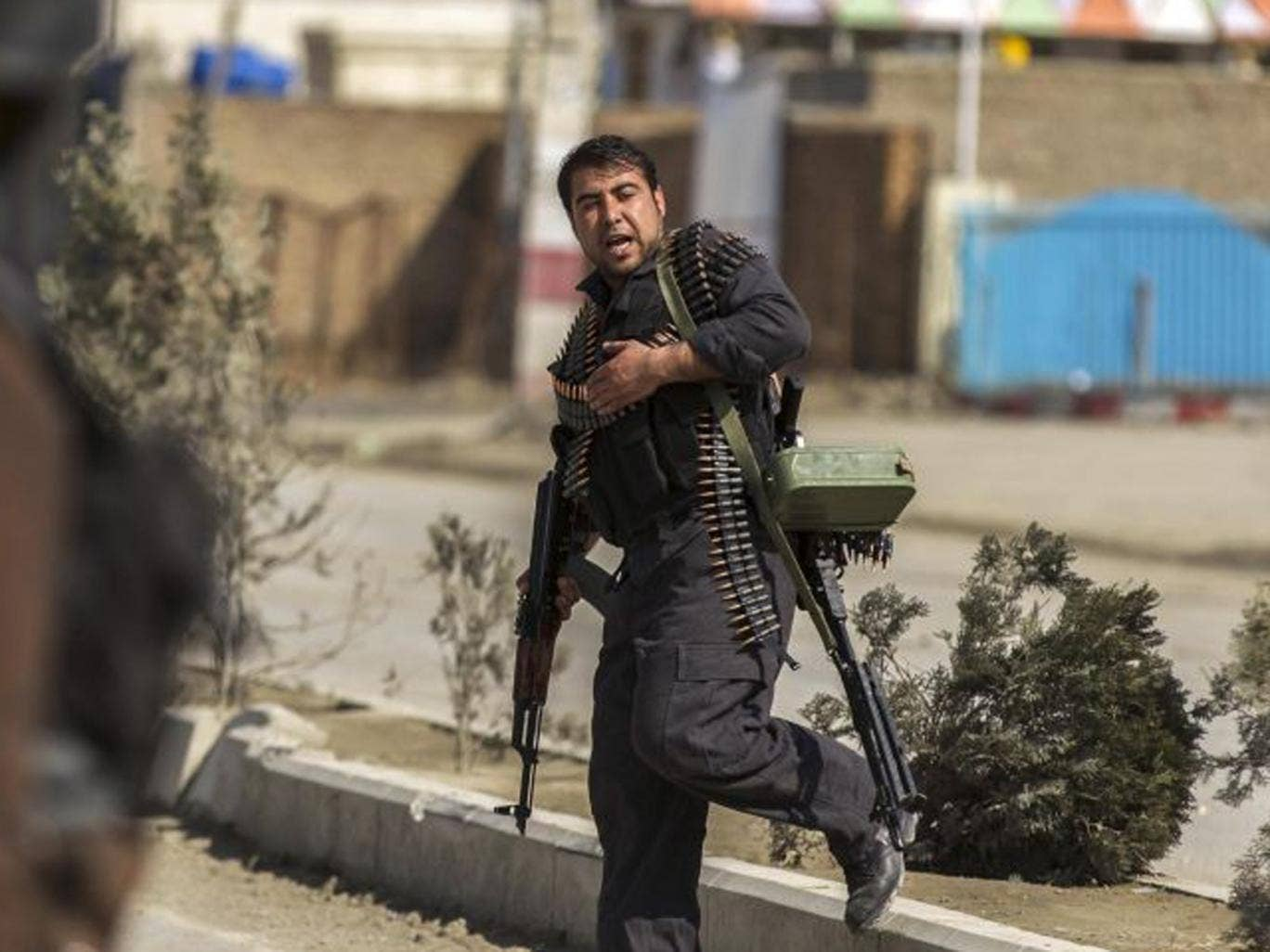 A policeman arrives at the Independent Election Commission office during the attack by insurgents