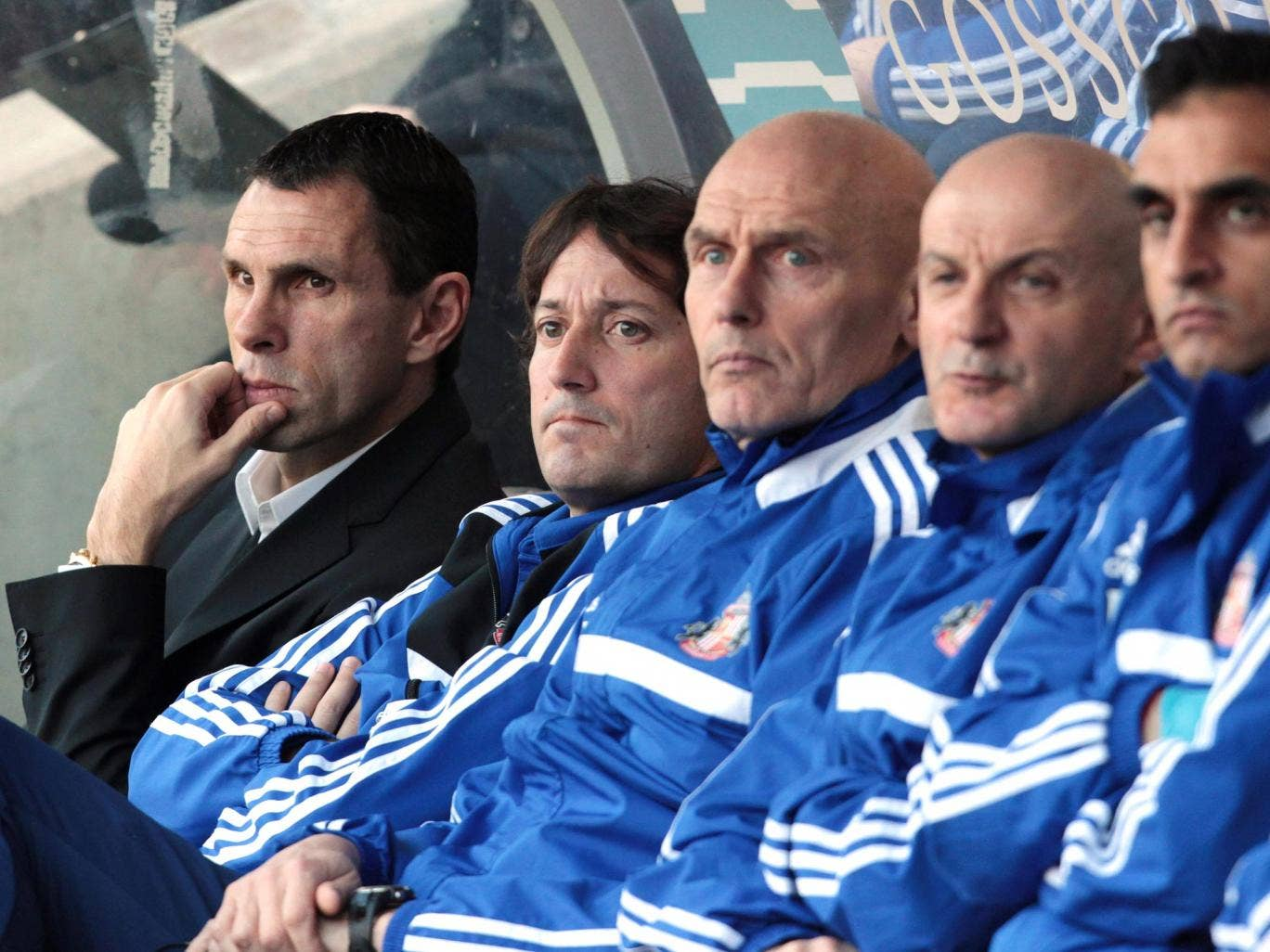 Gus Poyet sits in the dugout alongside his coaching staff