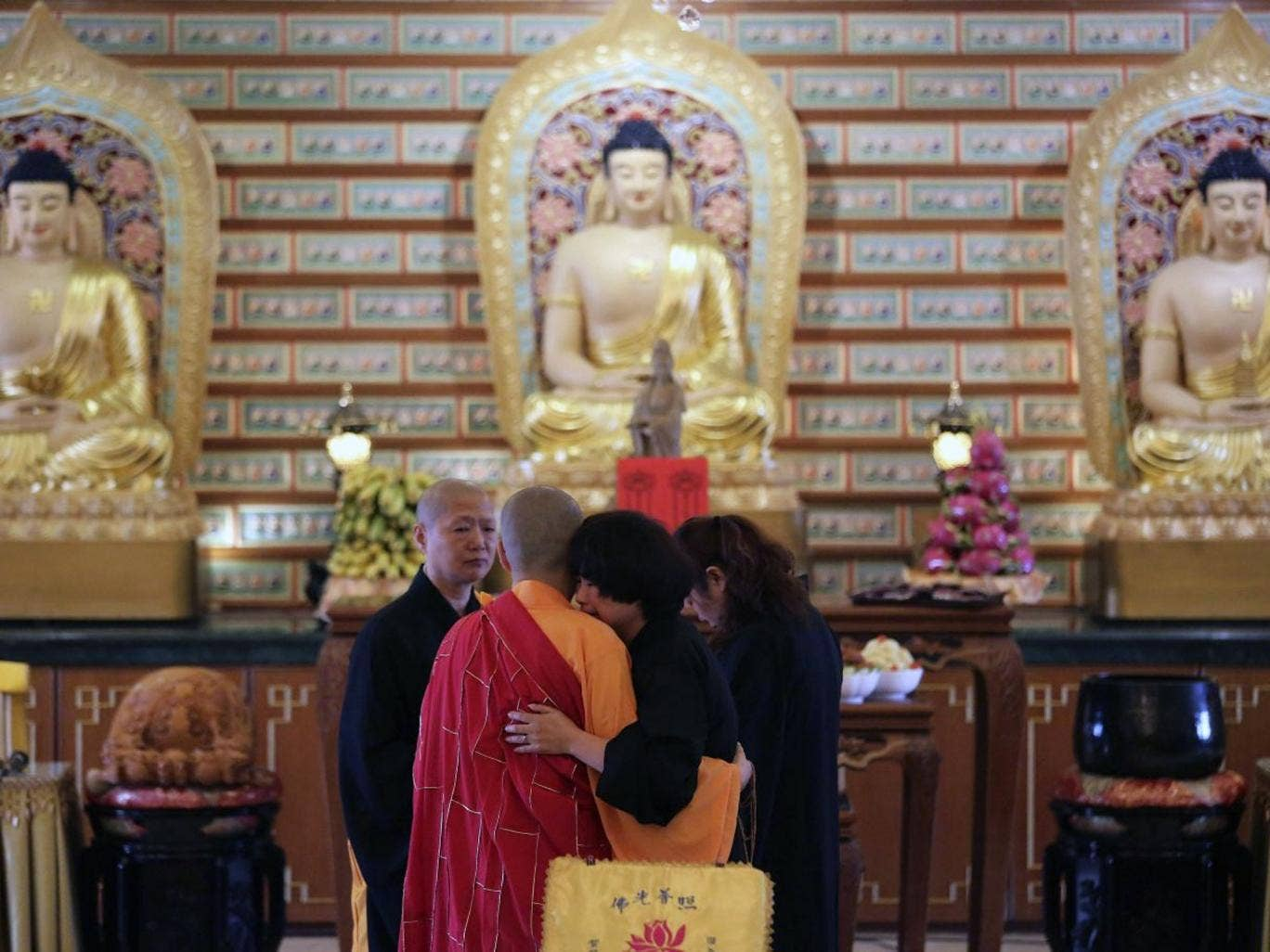 A Chinese relative of passengers on board the missing Malaysia Airlines Flight MH370 is comforted by a monk as she breaks into tears following prayers at a Buddhist temple in Petaling Jaya, Malaysia, Monday March 31, 2014. Relatives from China are in the