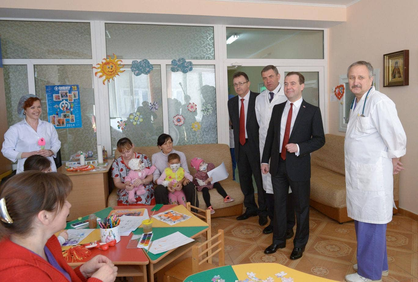 Russian Prime Minister Dmitry Medvedev (2-R) flanked by hospital's chief physician Alexandr Astakhov (3-R) visits the Simferopol Republican Pediatric Hospital in Simferopol, Crimea