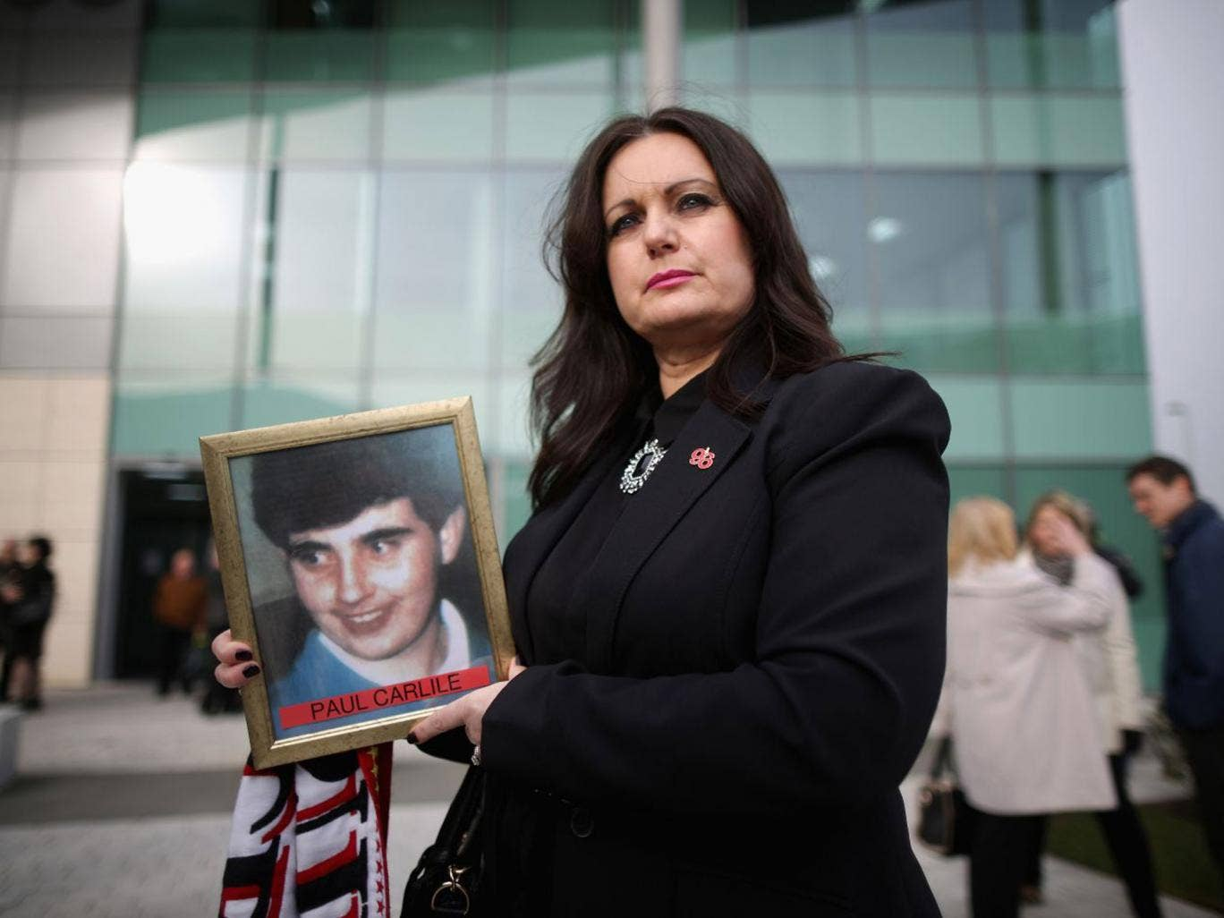 Donna Miller, carrying a picture of her brother Paul Carlile, who died aged 19 at Hillsborough, arrives for the start of the new inquest