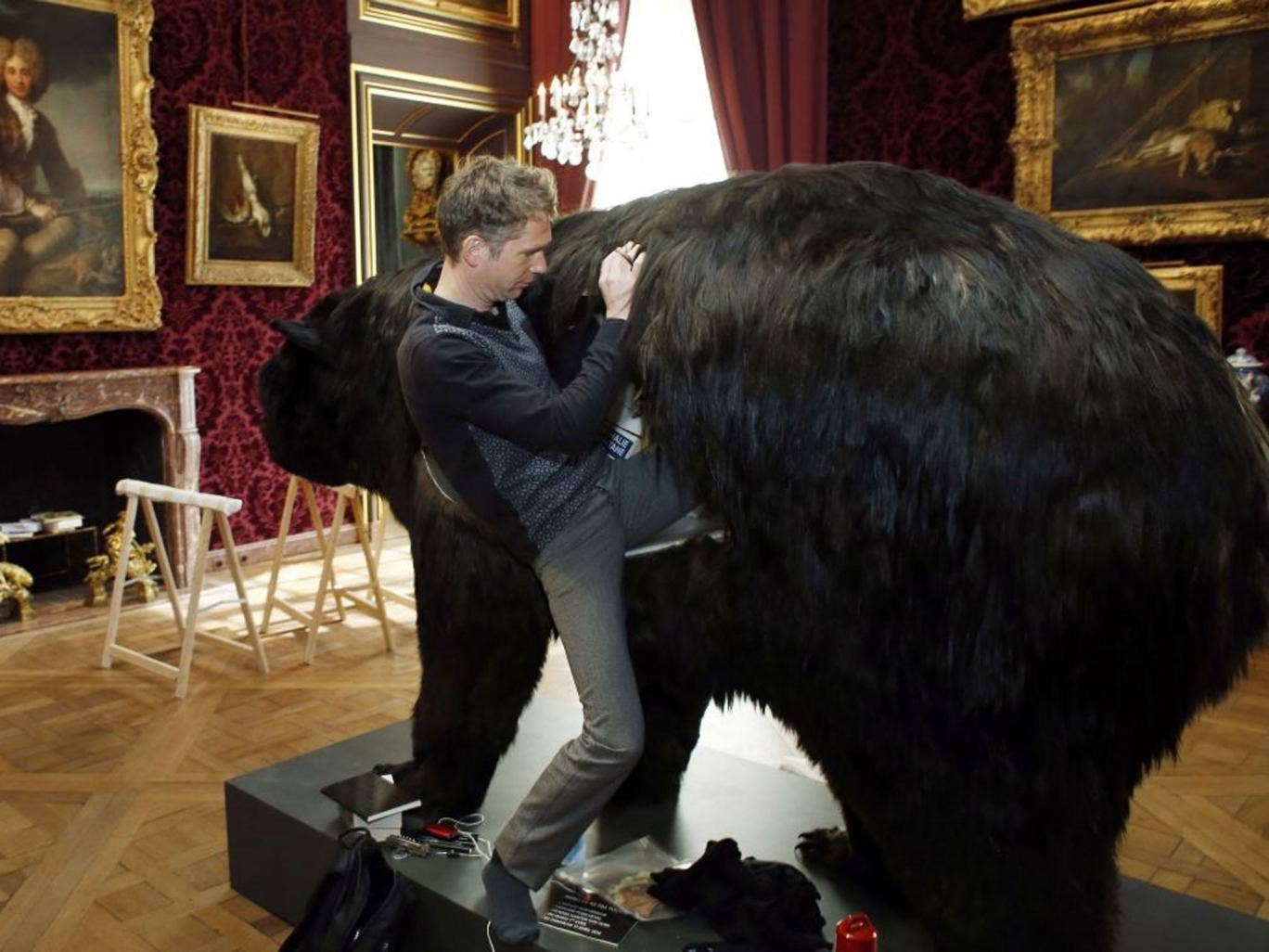 French artist Abraham Poincheval climbs into a fake bear, on March 31, 2014, in Paris, the day before starting an artistic performance in which he will spend thirteen days in the bear's skin, at the Hunting and Wildlife Museum ('Musee de la Chasse et de l
