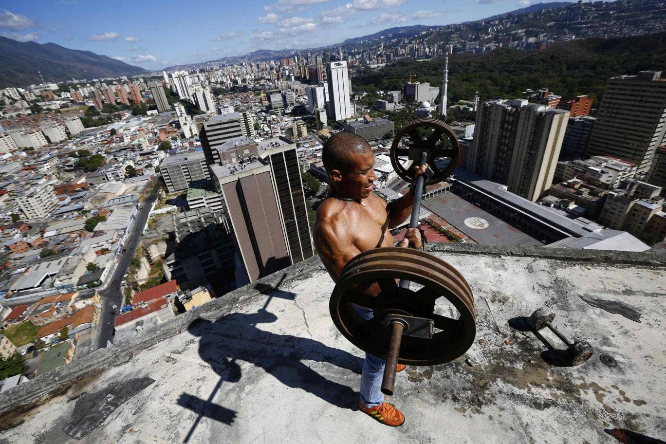Gabriel Rivas (30) lifts weights on a balcony on the 28th floor of the 'Tower of David' skyscraper in Caracas