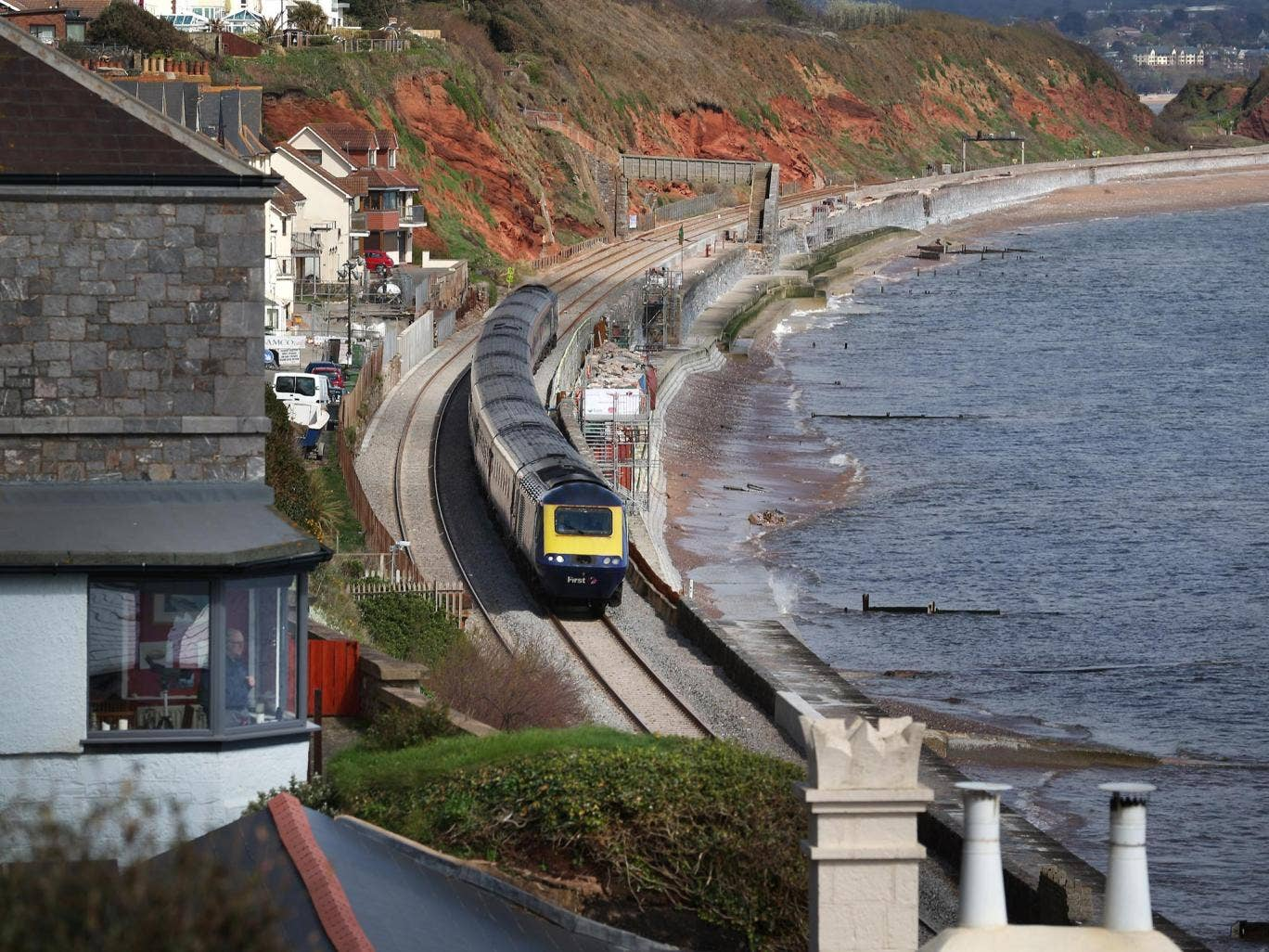A train passes along the rebuilt track in Dawlish