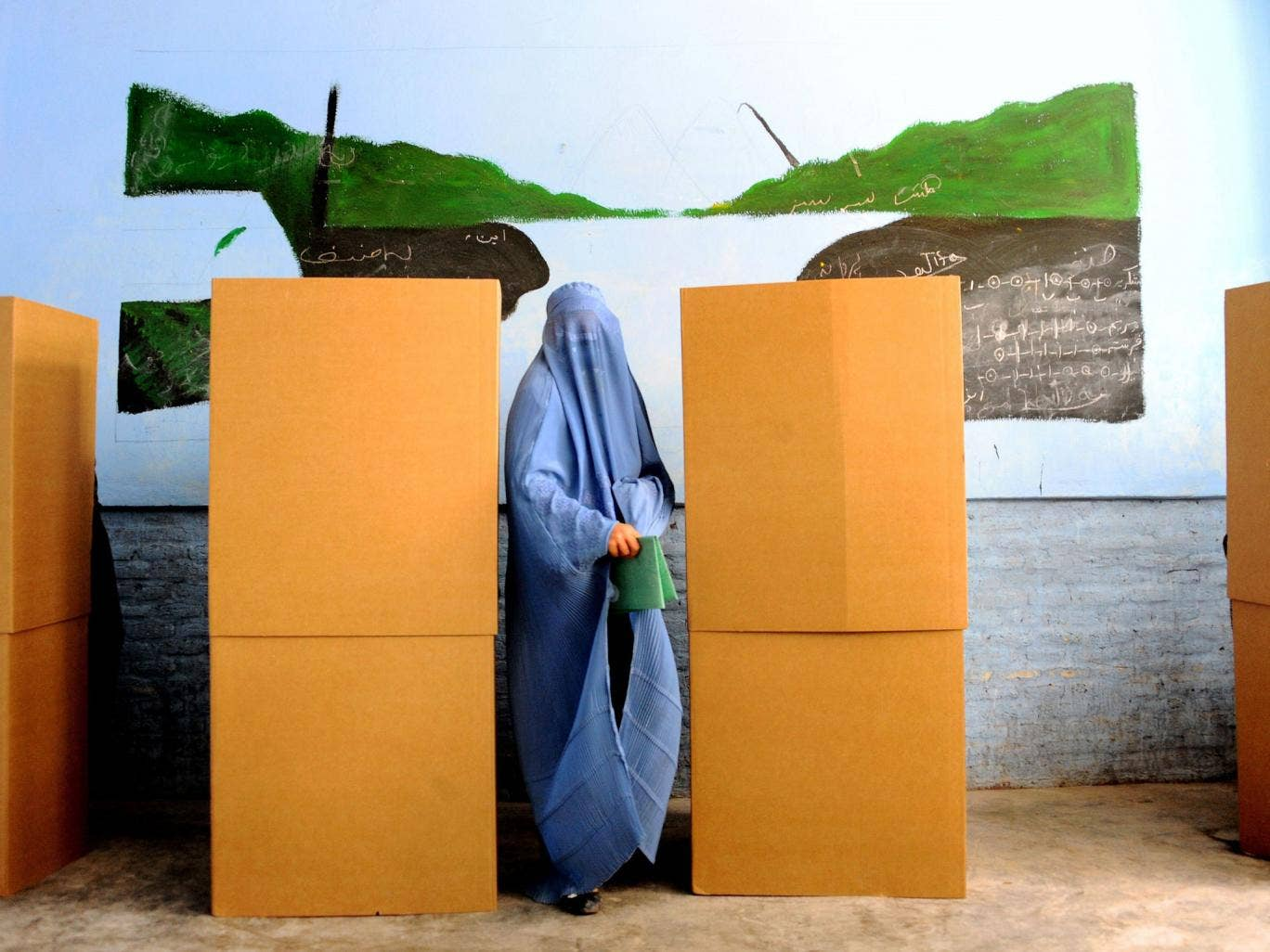 An Afghan woman shows her inked finger after voting at a polling station in the northwestern city of Herat