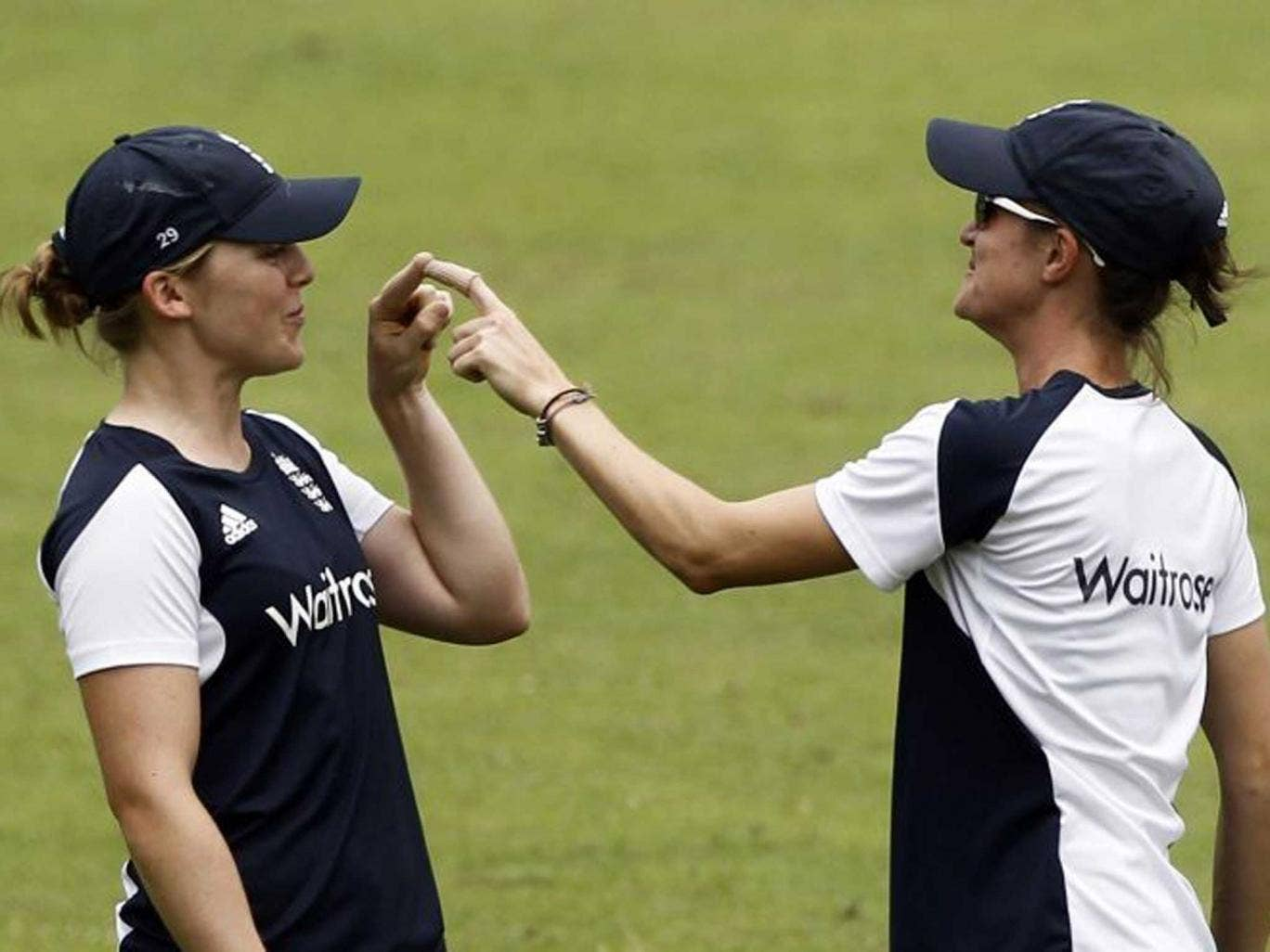Finger on pulse: England bowler Jodie Dibble (left) finds a novel way of connecting with her team-mate