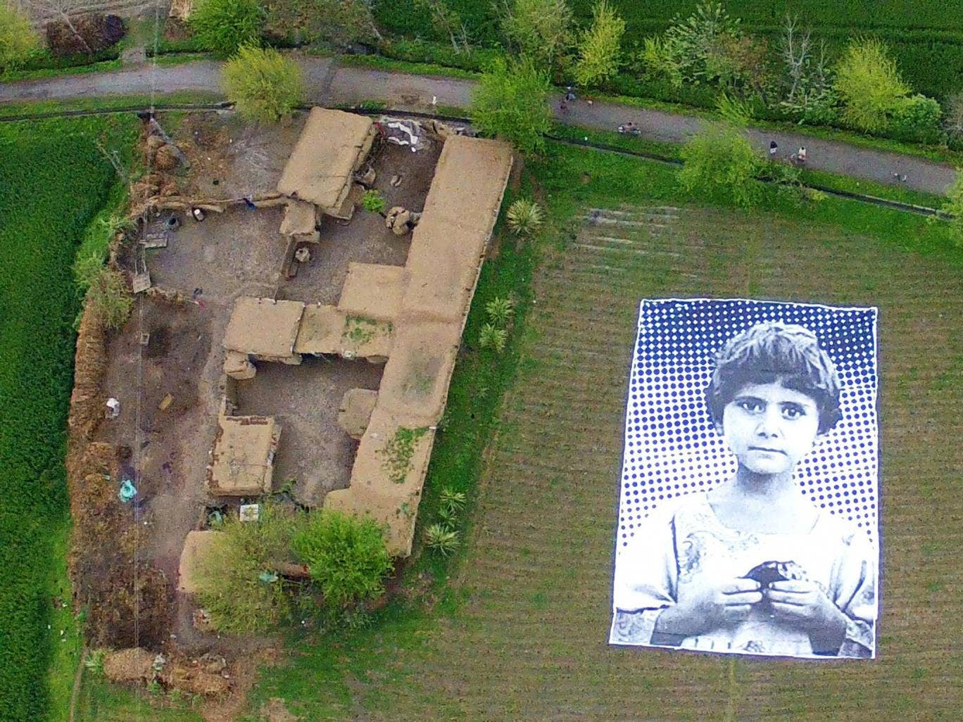 """A poster bearing the image of a Pakistani girl whose parents, lawyers say, were killed in a drone strike, lies in a field at an undisclosed location in the northwestern Khyber-Pakhtunkhwa province. A group of artists in Pakistan are hoping to generate """"em"""
