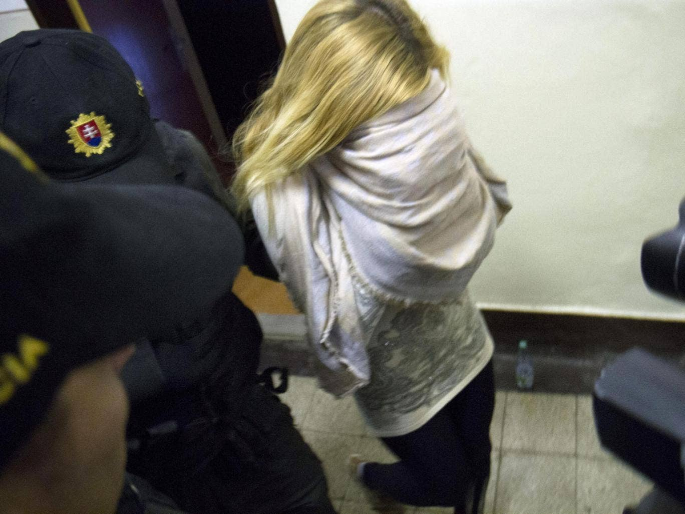 Slovakian model Mayka Marica Kukucova is escorted by the police from the Regional Court in Trencin, Slovakia