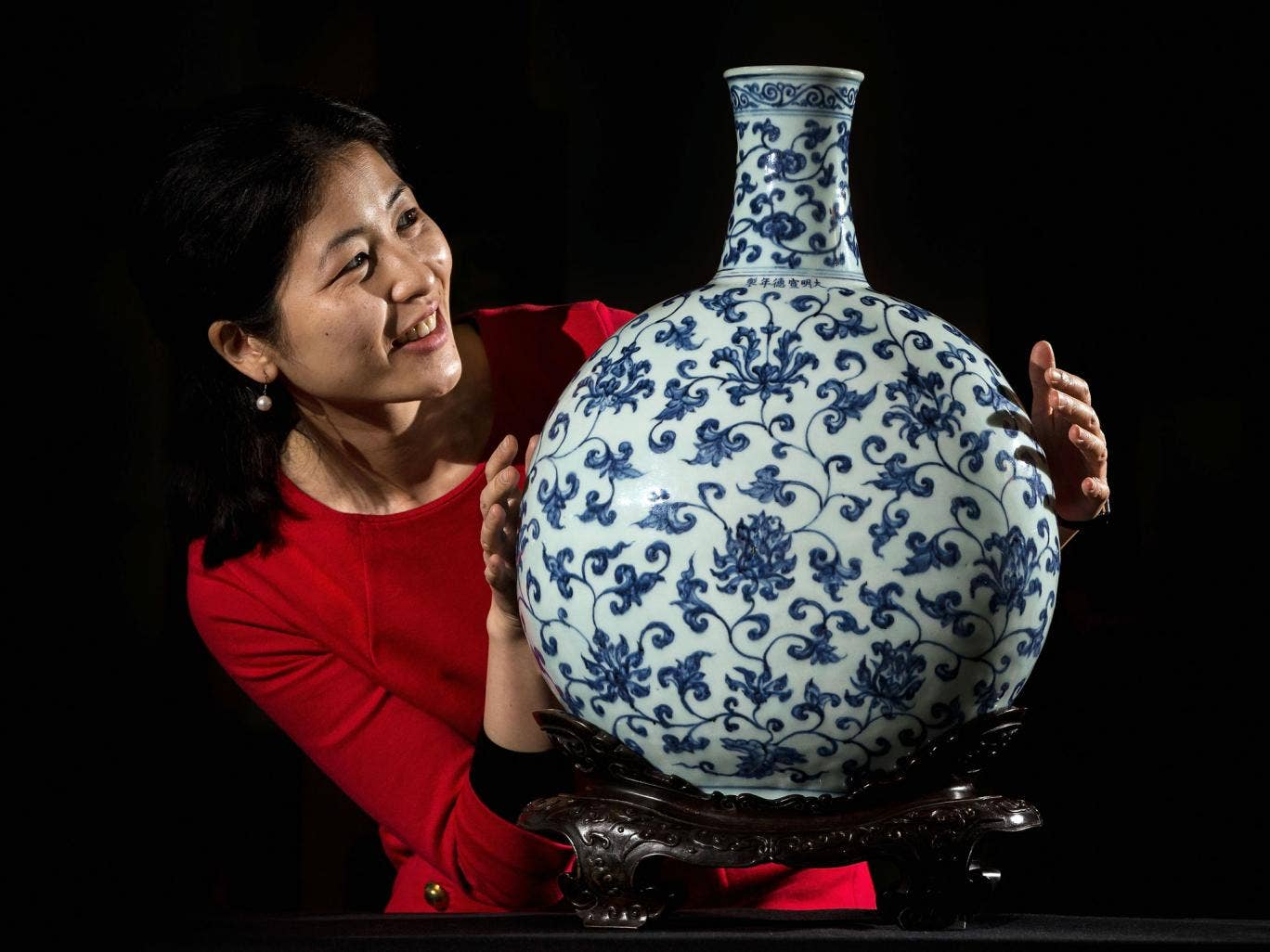 A British Museum employee poses behind a 15th century Imperial Ming Vase, during a photocall at British Museum on January 8, 2014 in London, England. The porcelain vase makes up part of the 'Made in China' exhibition and will tour the country as part of t