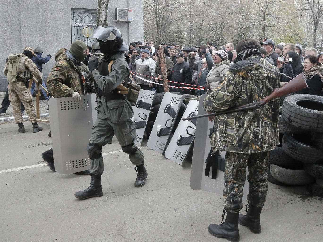 Pro-Russian activists occupy the police station carrying riot shields as people watch on, in the eastern Ukraine town of Slovyansk