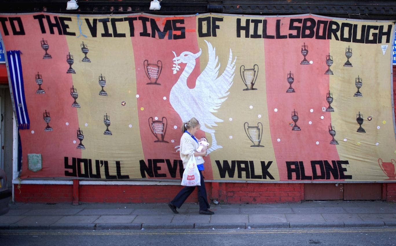A woman walks past a Hillsborough tribute banner as fans arrive in Anfield for a memorial service marking the 25th anniversary of the Hillsborough Disaster at Anfield stadium in Liverpool