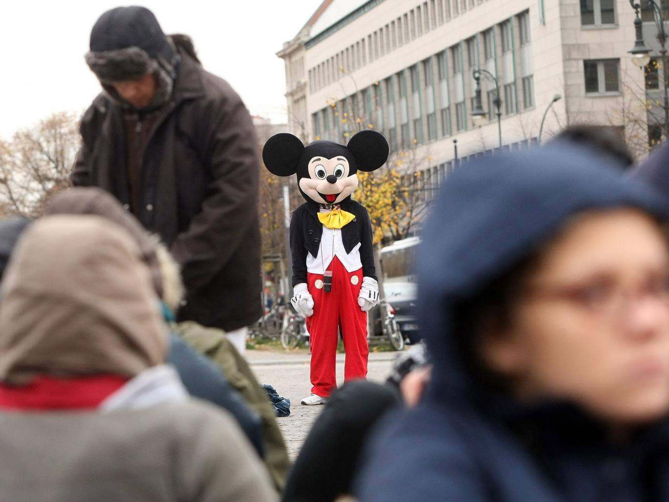 A street performer dressed as Mickey Mouse stands near protesting refugees as they stage a hunger strike in front of the Brandenburg Gate on October 25, 2012 in Berlin, Germany. The demonstrators, predominantly from Iran, Afghanistan and Iraq are subsisti