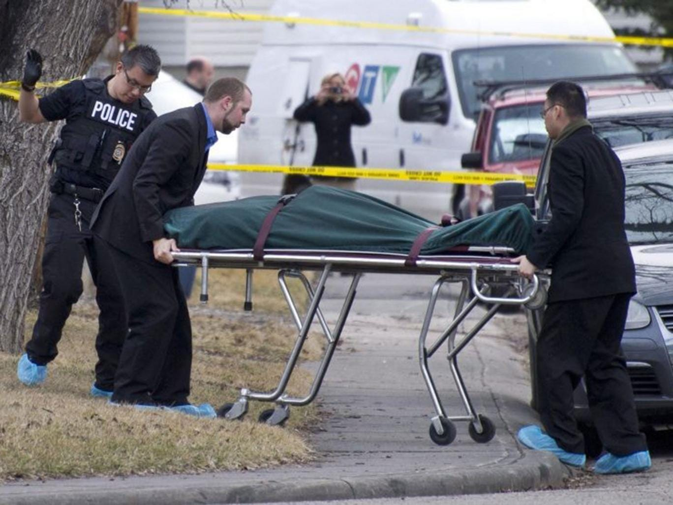 Police remove a body from the scene the stabbing in Calgary