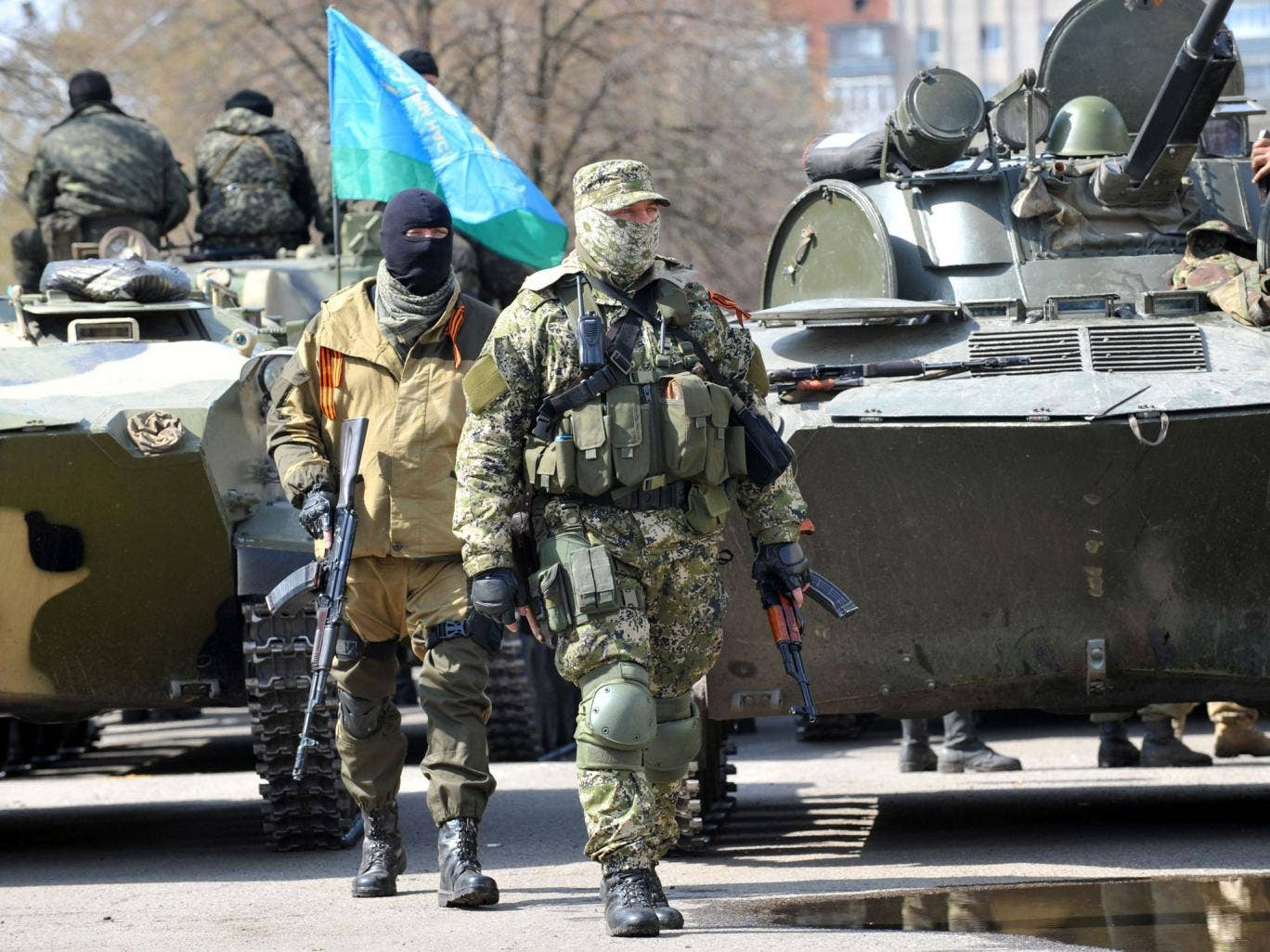 Armed men wearing military fatigues gather by Armoured Personnel Carriers (APC) as they stand guard outside the regional state building seized by pro-Russian separatists in the eastern Ukrainian city of Slavyansk