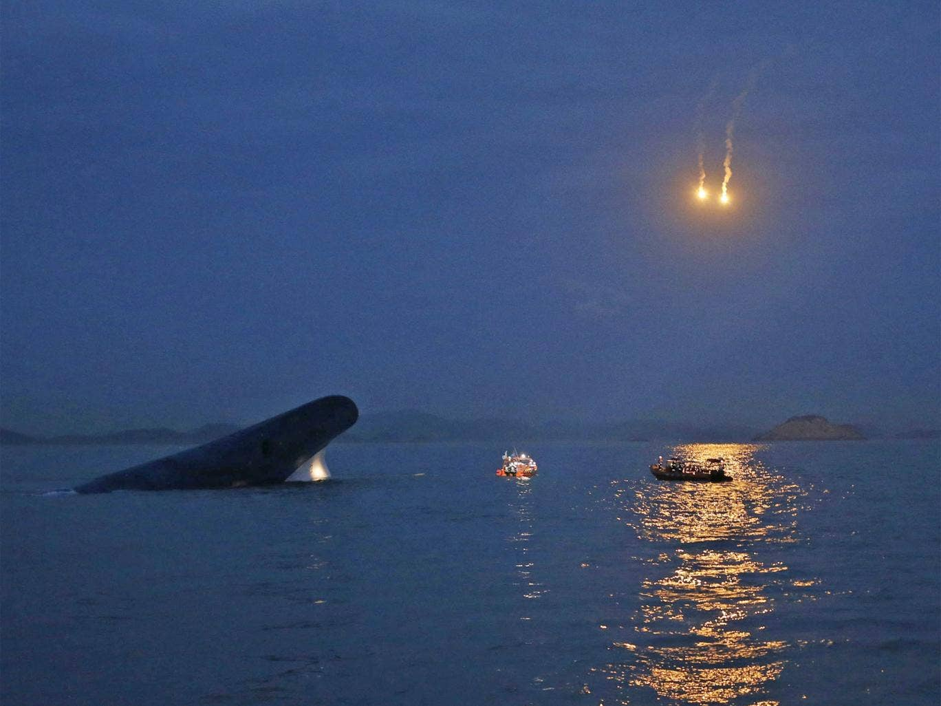 South Korean ferry 'Sewol' is seen sinking at the sea off Jindo, as lighting flares are released for a night search