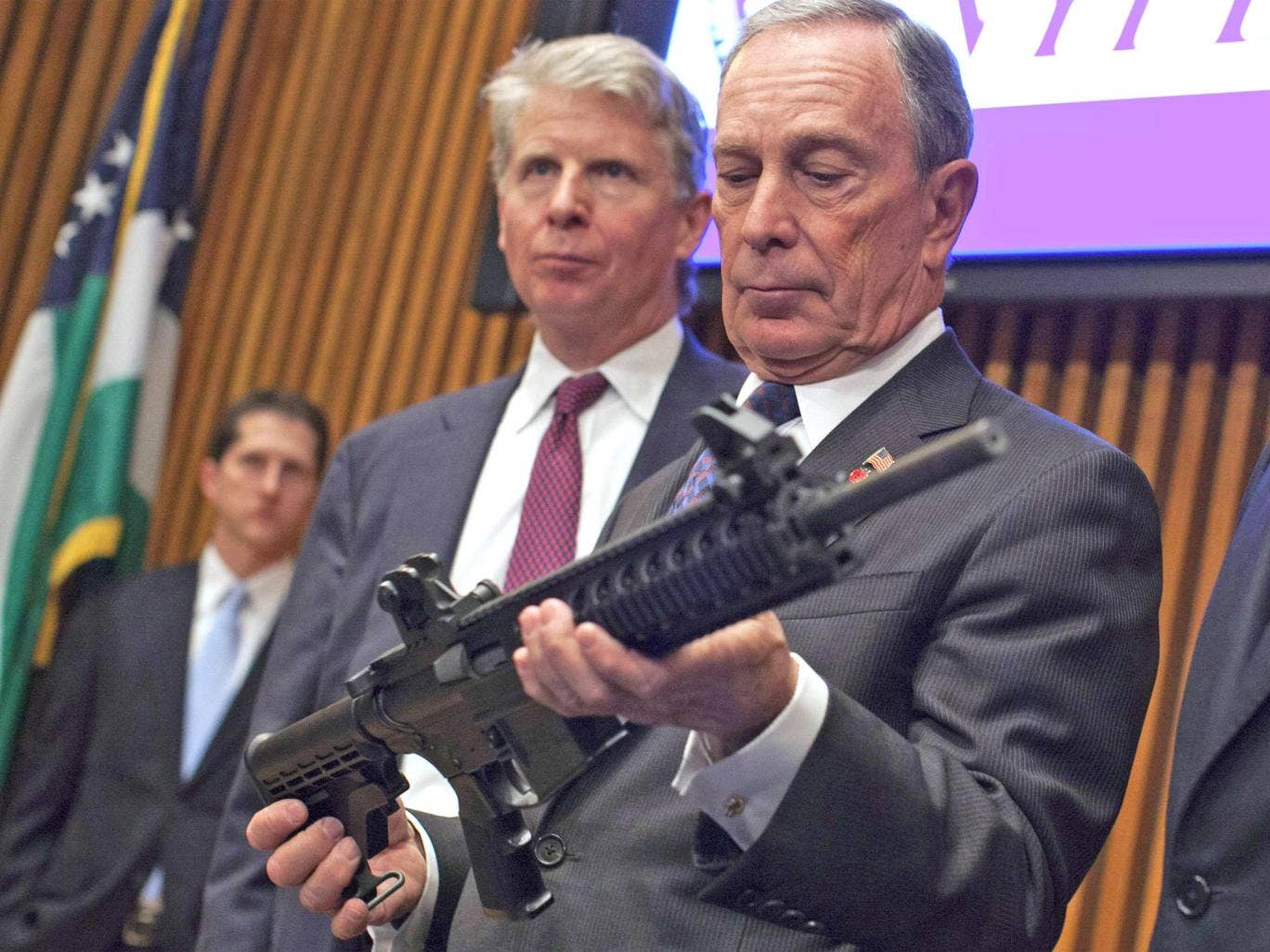Michael Bloomberg examines a gun confiscated by police in New York during his term as the city's mayor in 2012