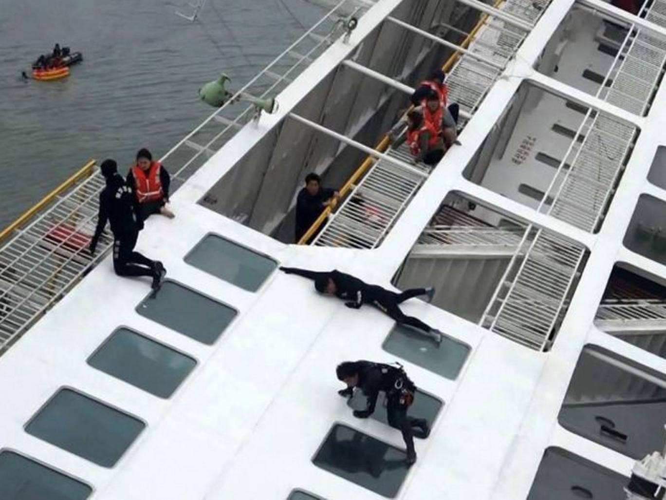 "Maritime officers (in black) try to rescue passengers (in orange coloured life vests) onboard South Korean ferry ""Sewol"" which capsized off Jindo April 16"
