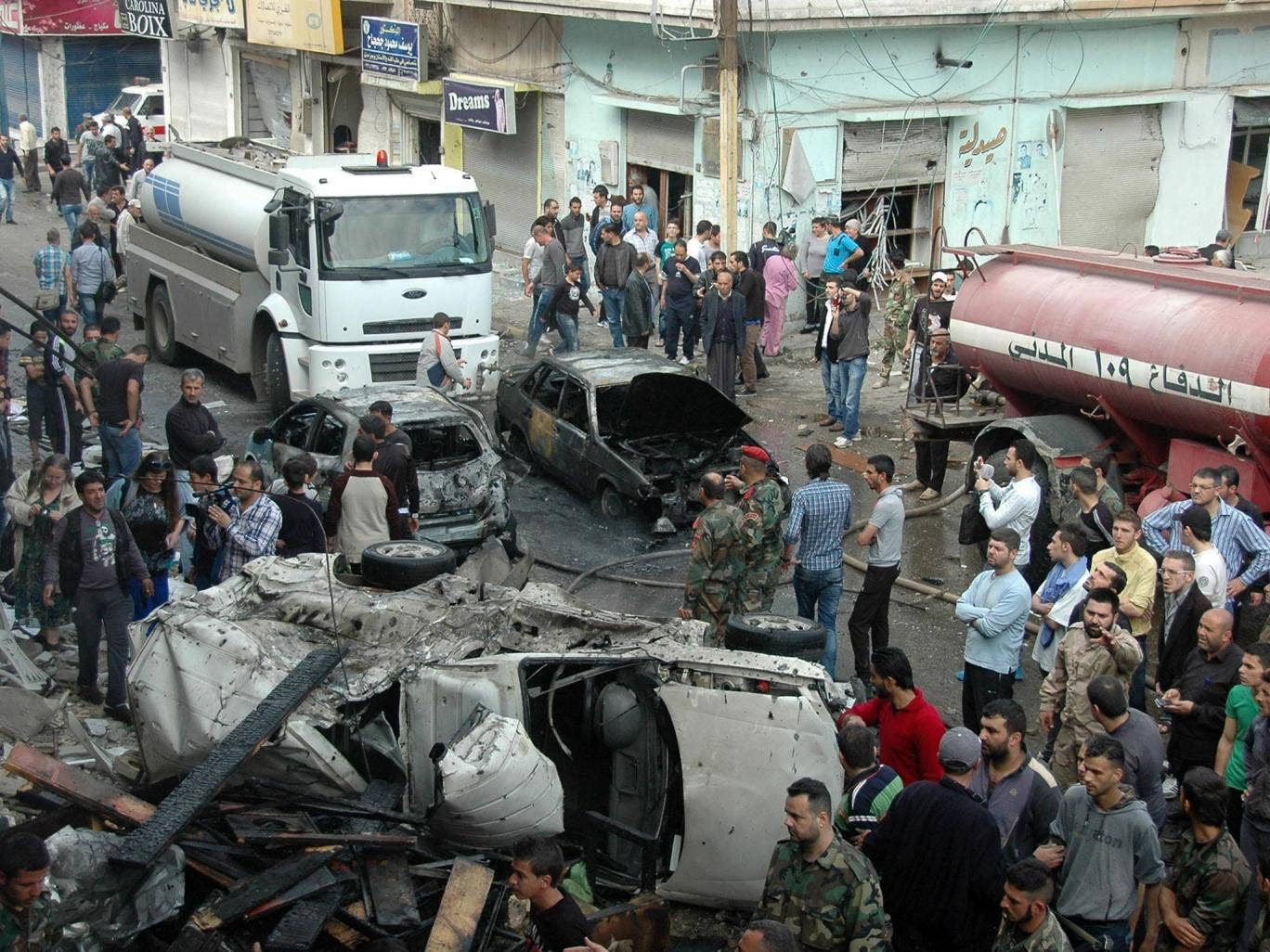 Security and emergency medical personnel work at the site of a car bomb explosion in al-Ushaq street in Ekremah neighboorhood in Syrias central city of Homs