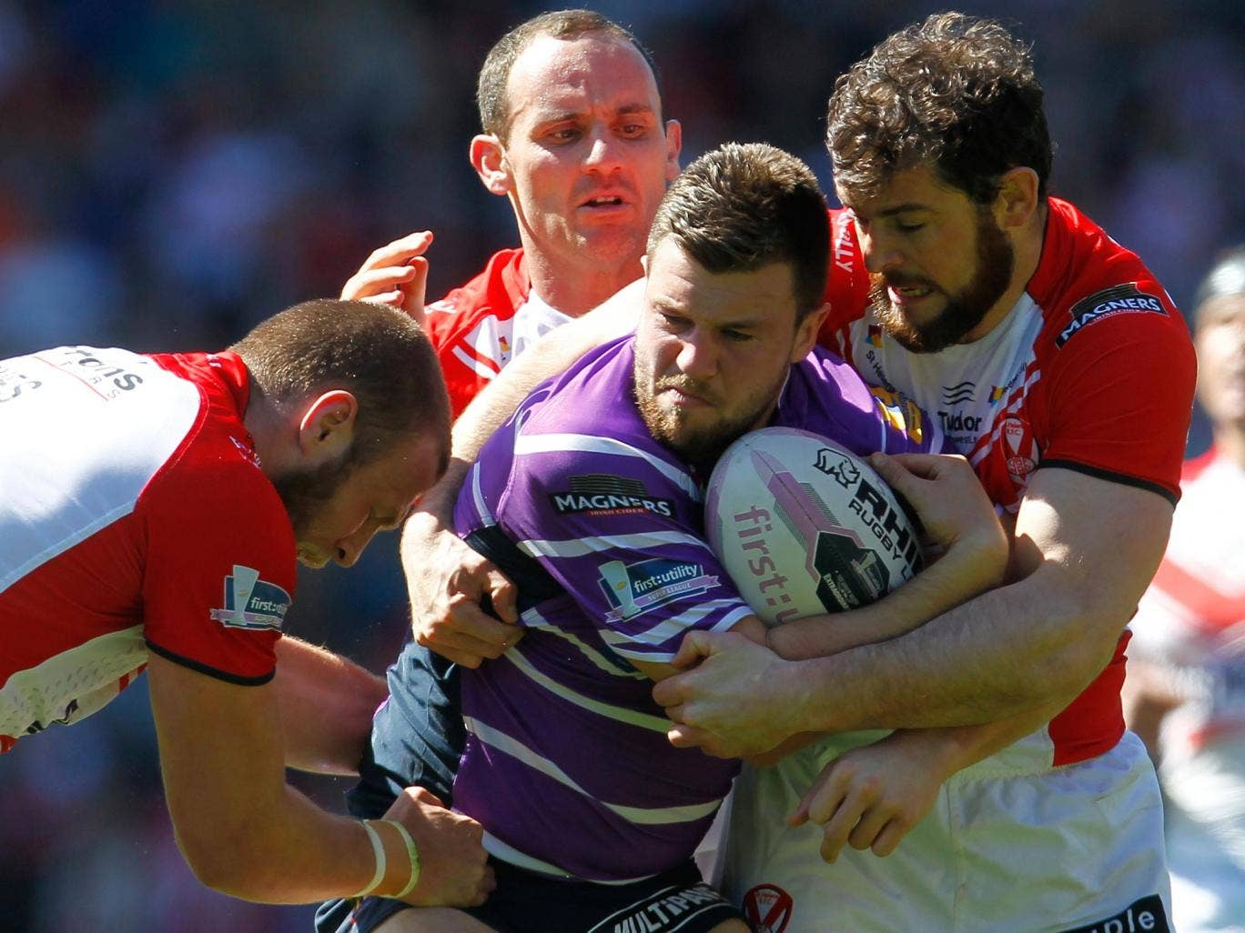 Darrell Goulding of Wigan is tackled by Josh Jones (L), Lance Hohaia and Paul Wellens (R) during the Super League match between St Helens and Wigan