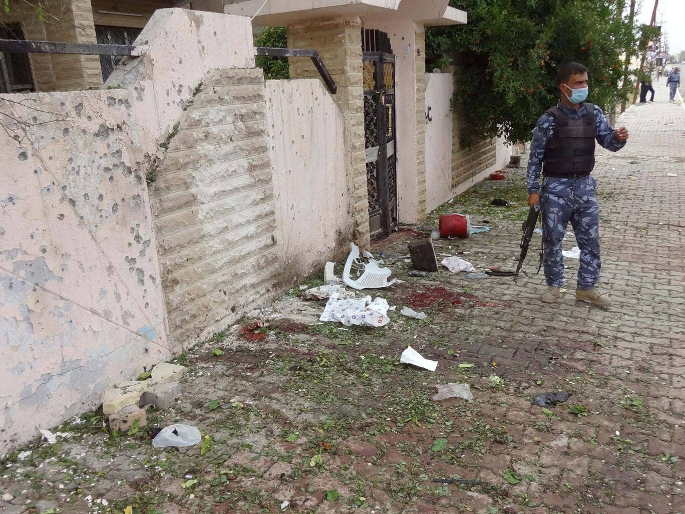 An Iraqi policeman inspects the site of a suicide bombing outside a polling station in the northern Iraqi city of Kirkuk