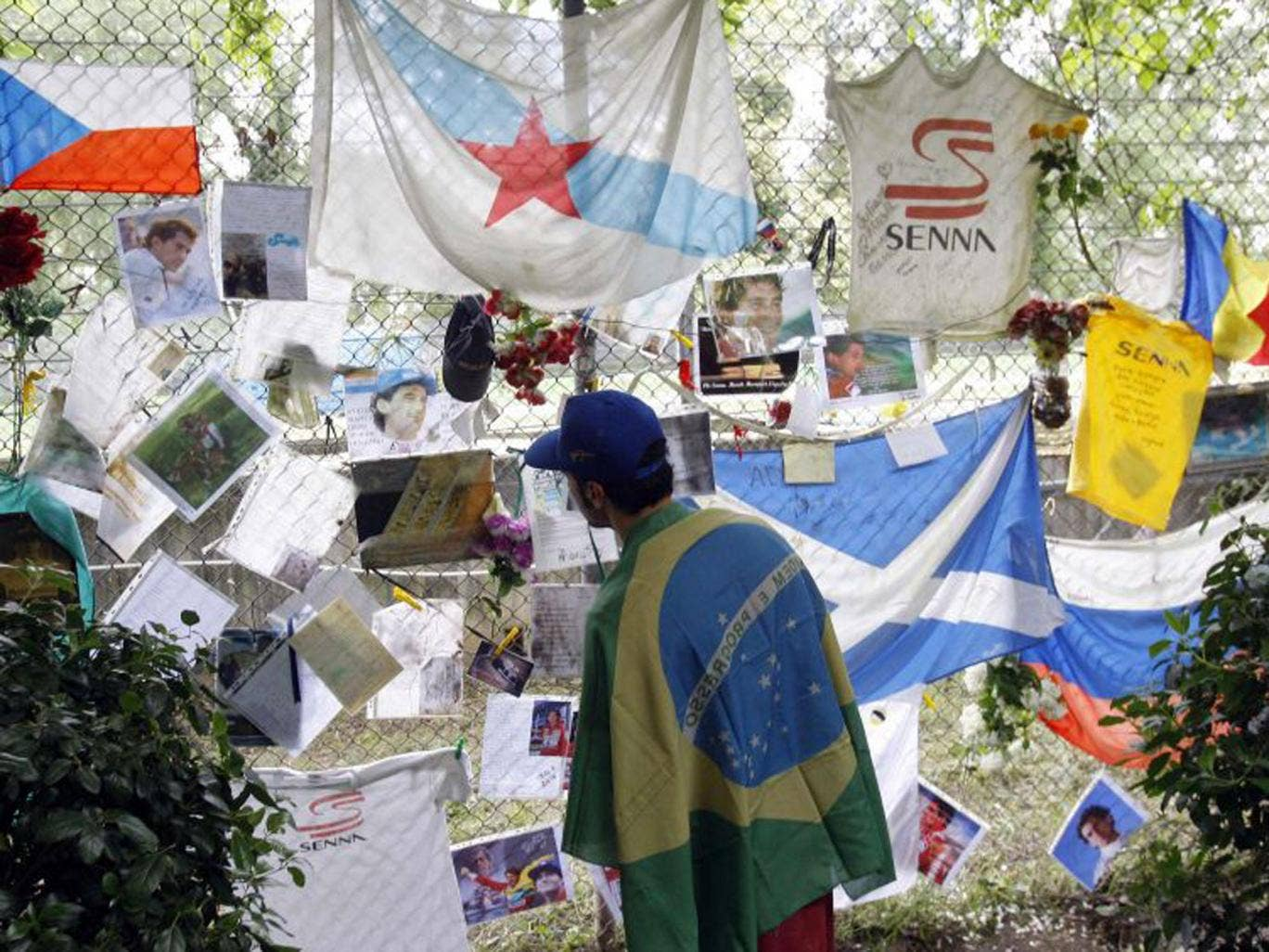 A fan of Brazilian Formula One driver Ayrton Senna reads handwritten notes and messages left at a statue memorial at the Imola race track today