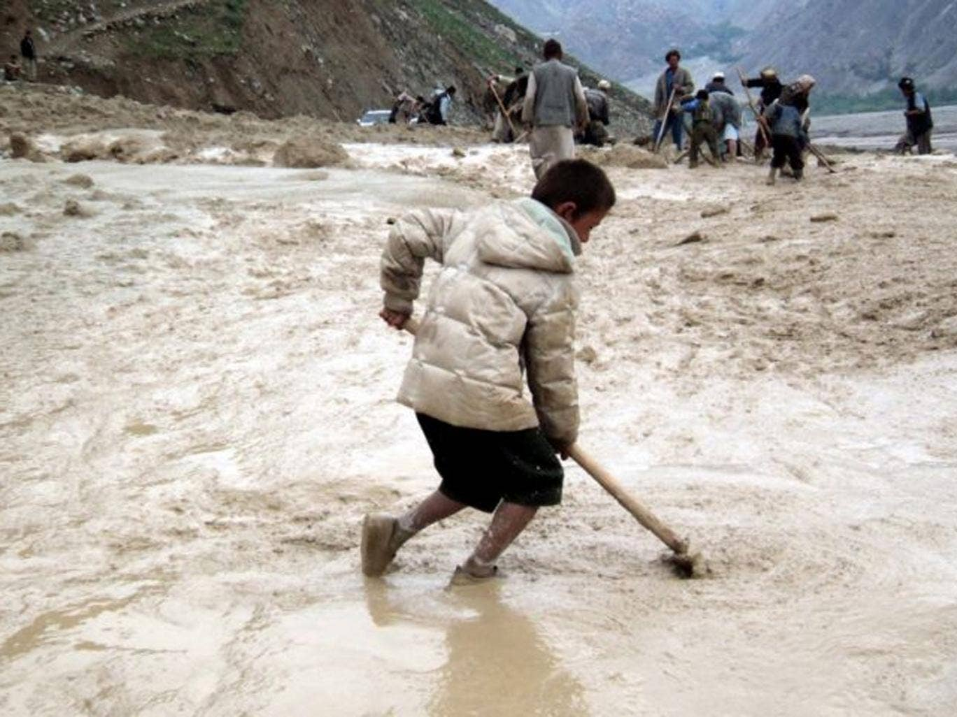 Workers removing debris from a road affected by flash floods in Badakhshan, Afghanistan. As in 2012, the area has been hit again by a comparable disaster. At least 2,100 people are feared dead on 02 May 2014, after a mudslide, caused by heavy rainfalls, b