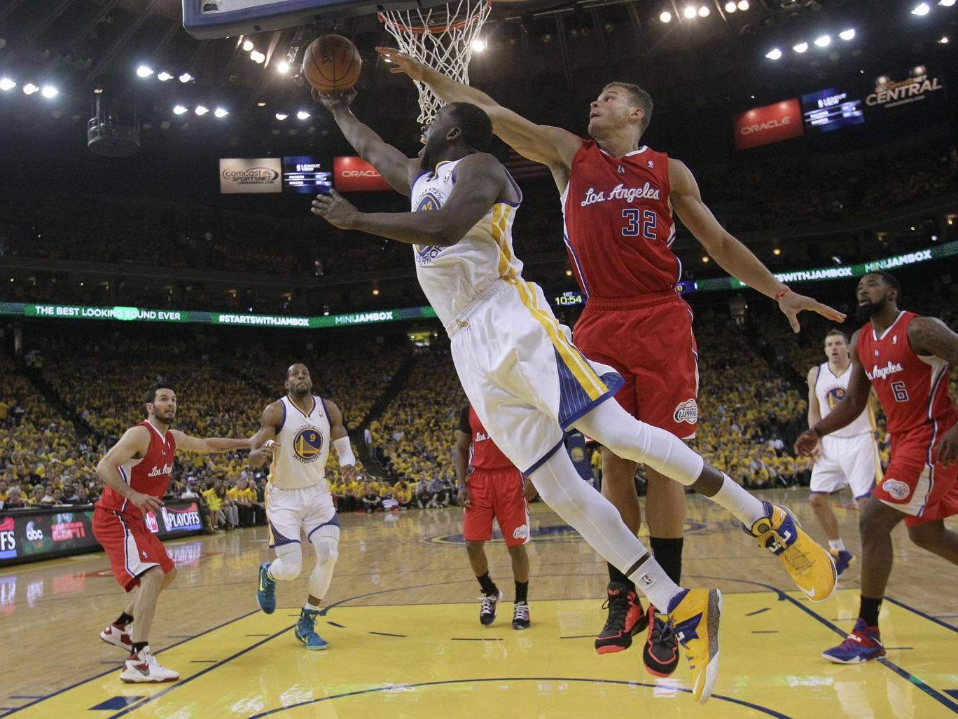 Golden State Warriors' Draymond Green, front left, shoots against the LA Clippers on Thursday