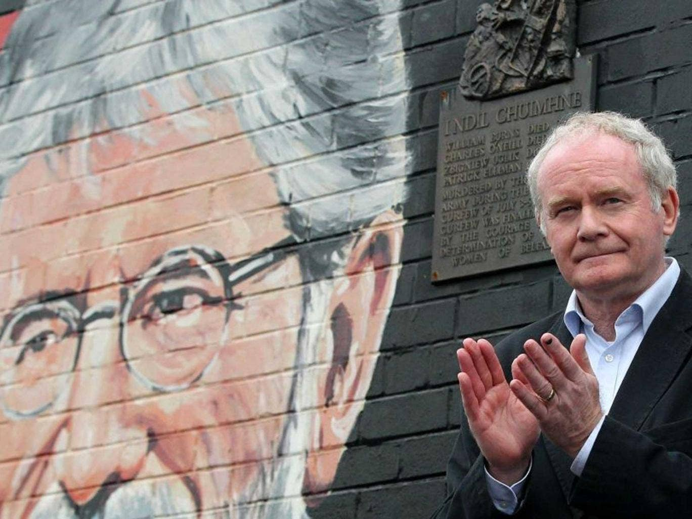 Deputy Martin McGuinness applauds the crowd as he speaks against a backdrop of a mural of detained Sinn Fein leader Gerry Adams