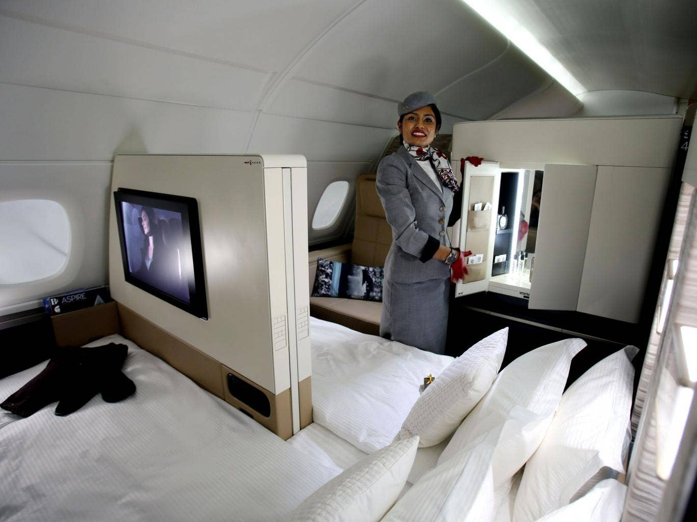 An Etihad Airways official stands inside a mock-up first class cabin,