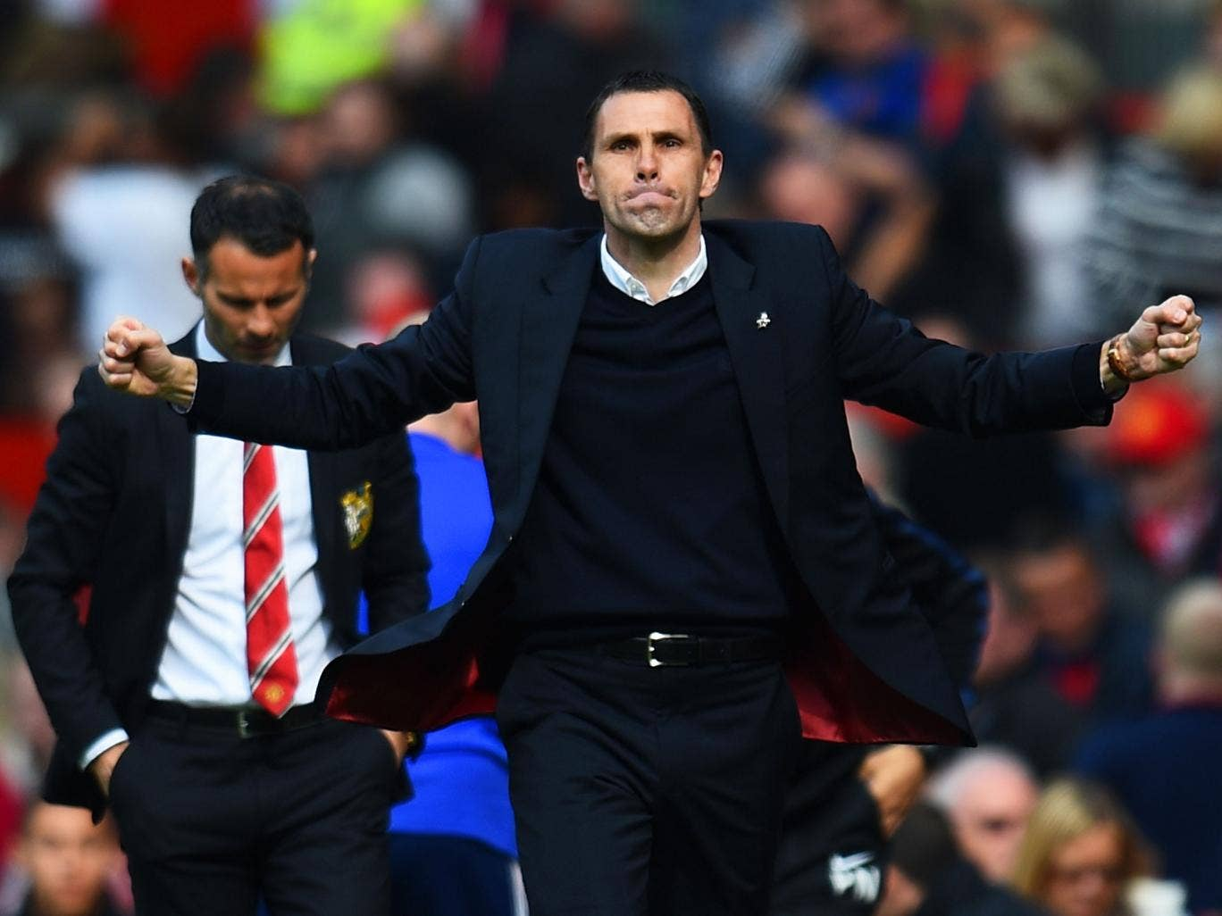 Sunderland manager Gus Poyet celebrates in front of a downcast Ryan Giggs