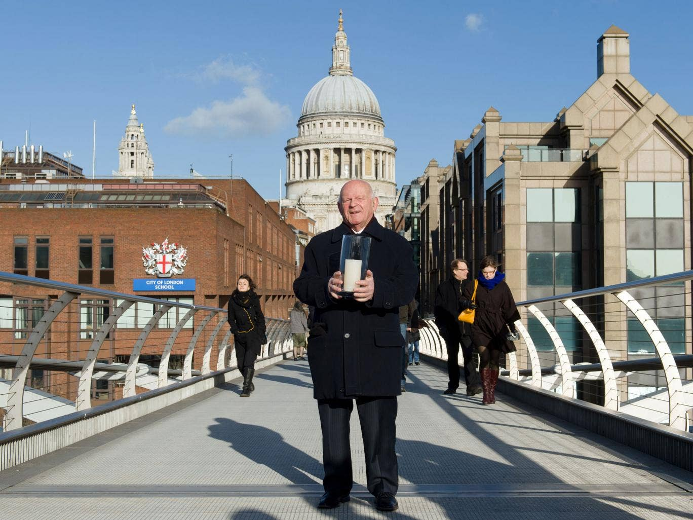 Holocaust survivor Ben Helfgott holds a memorial candle on the Millennium Bridge in London on Holocaust Memorial Day