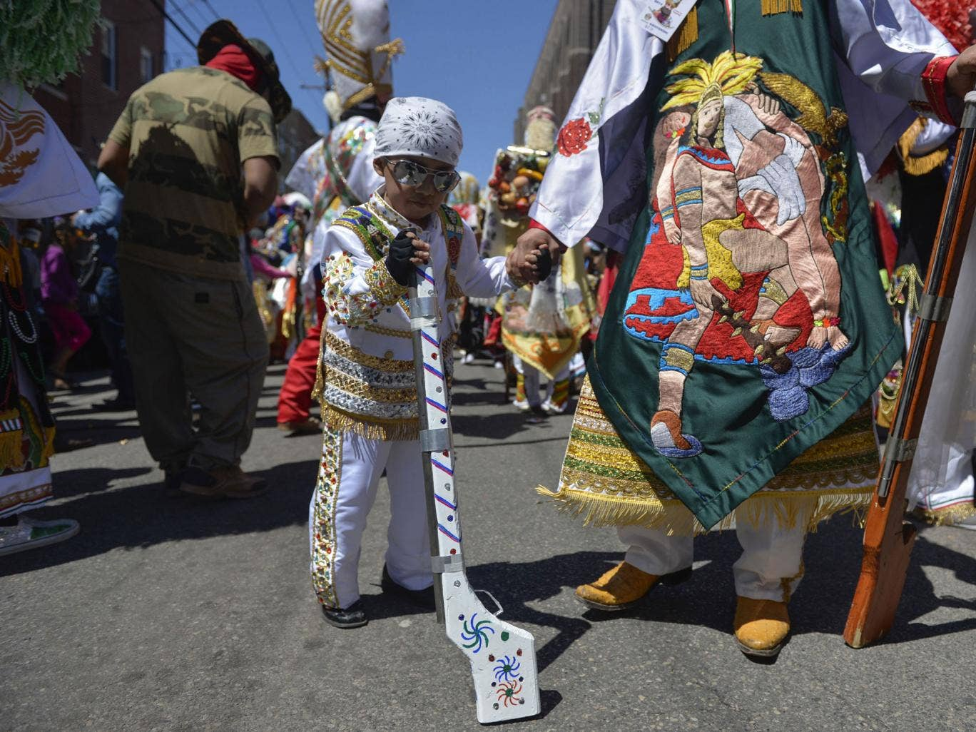 A boy dressed in carnival attire waits with his father before the Carnaval de Puebla, a traditional Mexican carnival celebration that re-enacts the Battle of Cinco de Mayo