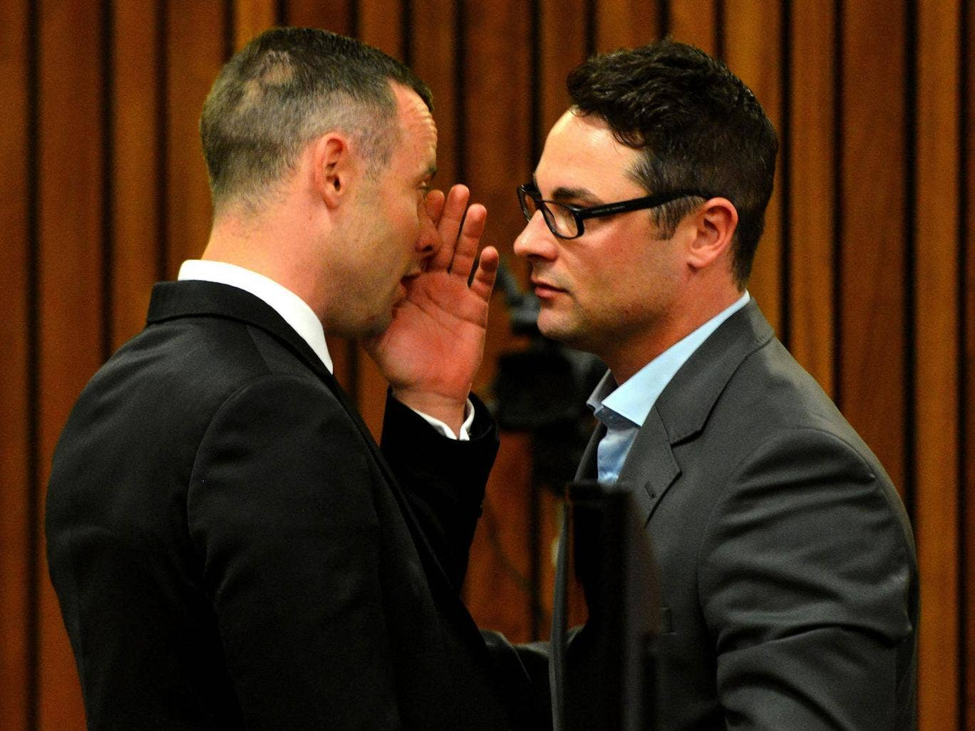 Oscar Pistorius talks with his brother Carl at the high court in Pretoria