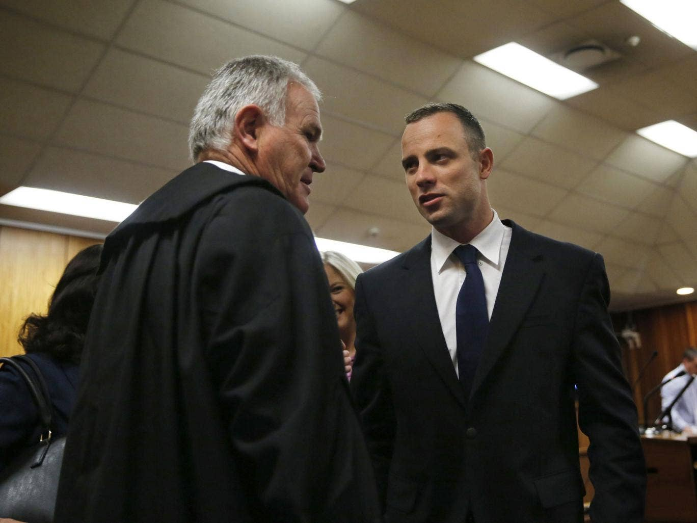 Oscar Pistorius  speaks with his defence lawyer Barry Roux at the North Gauteng High Court in Pretoria prior to a hearing of his murder trial