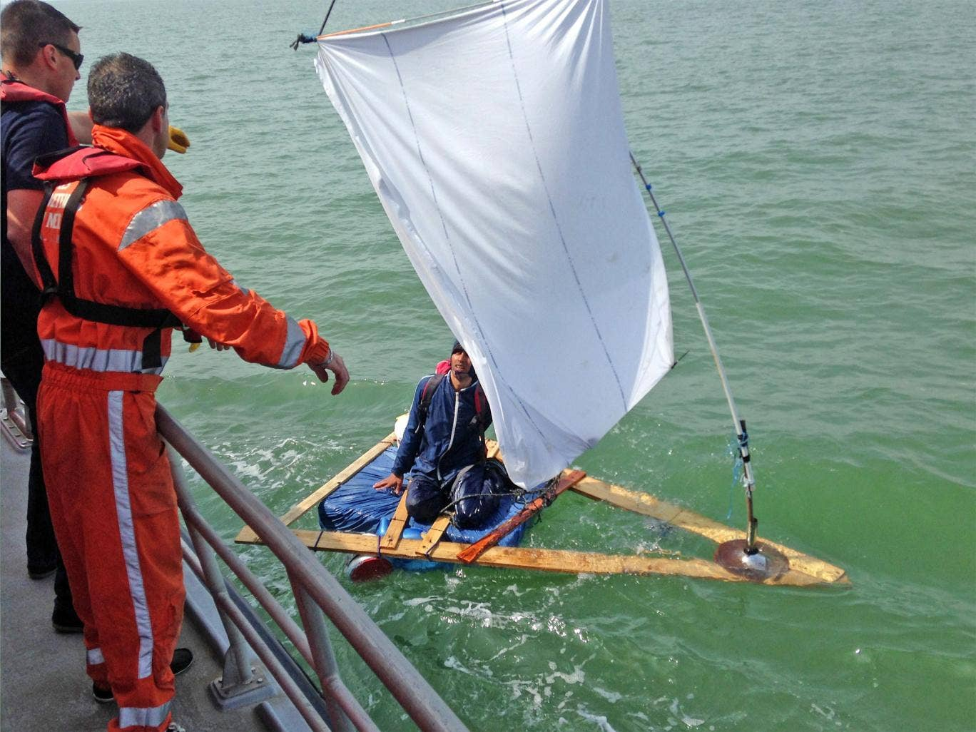 The French coastguard coming to the rescue of the Afghan aboard his home-made raft near Calais